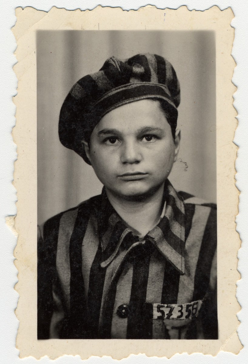 Studio portrait of Buchenwald survivor wearing a prisoner uniform.  The uniform of the boy probably originally belonged to Mozes Kuznitz (b. 12/7/26) in Sighet.  The children went to to a photo studio in town asking for a portrait of themselves in uniform.
