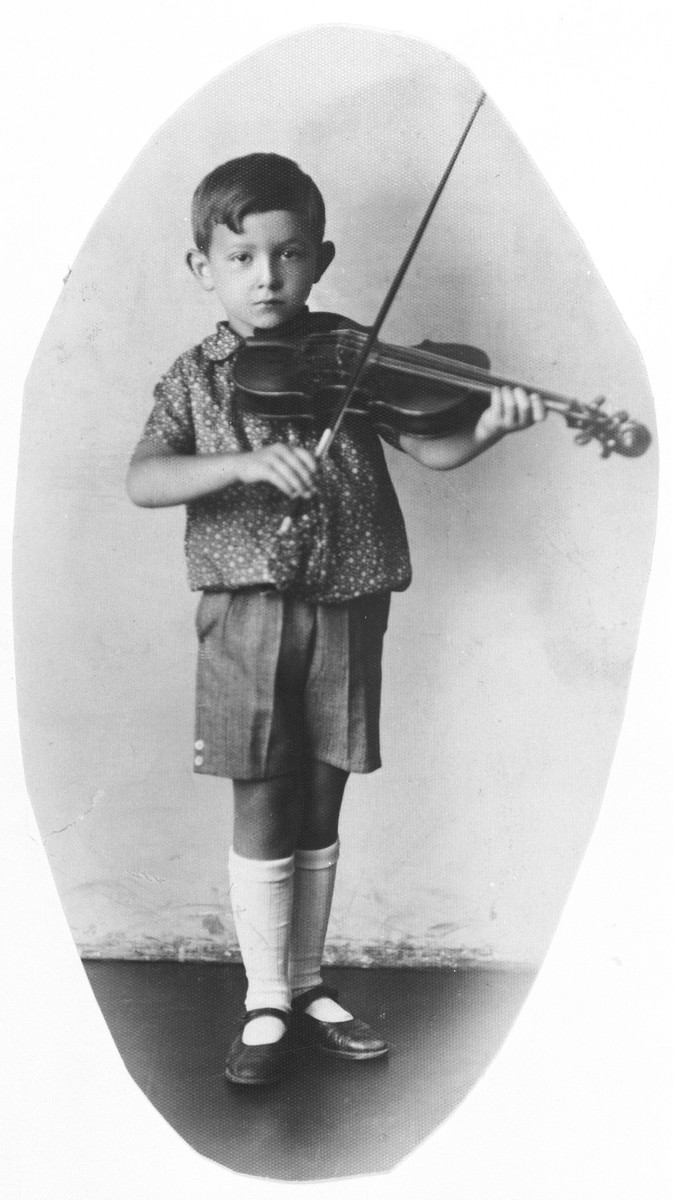 Studio portrait of Bronislaw Eichenholz playing his violin.