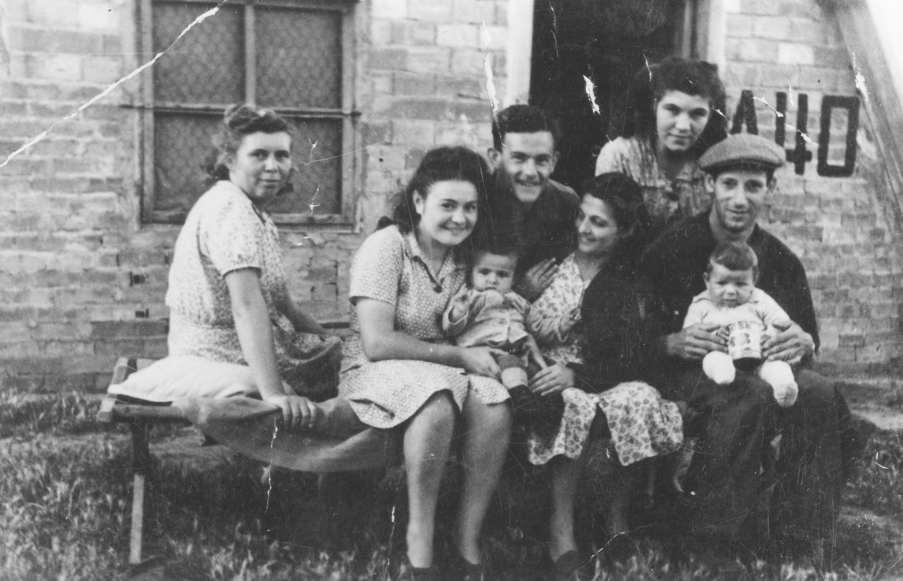 Group portrait of Jewish DPs outside a barracks in the Bari displaced persons camp.  Among those pictured are Izidor and Tauba Schachter with their baby Miriam Schachter (now Enright), on the far right; and Etta Gipsman (far left).  Etta  is wearing a dress made from fabric sent by relatives in America.