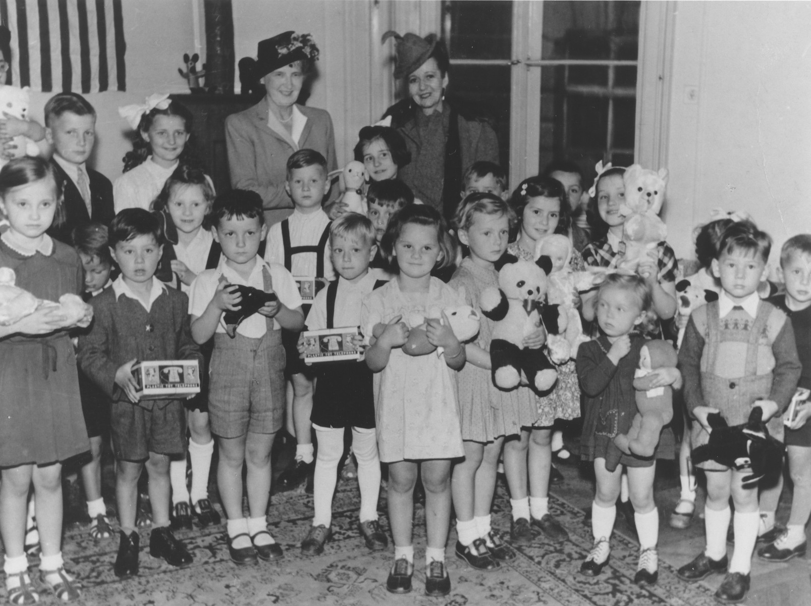 Group portrait of Jewish orphans who had survived Theresienstadt with the wife of Czech President Edvard Benes and the wife of the American Ambassador Laurence Steinhart.  Each child holds a newly received toy.  Among those pictured is Judis Baehr.