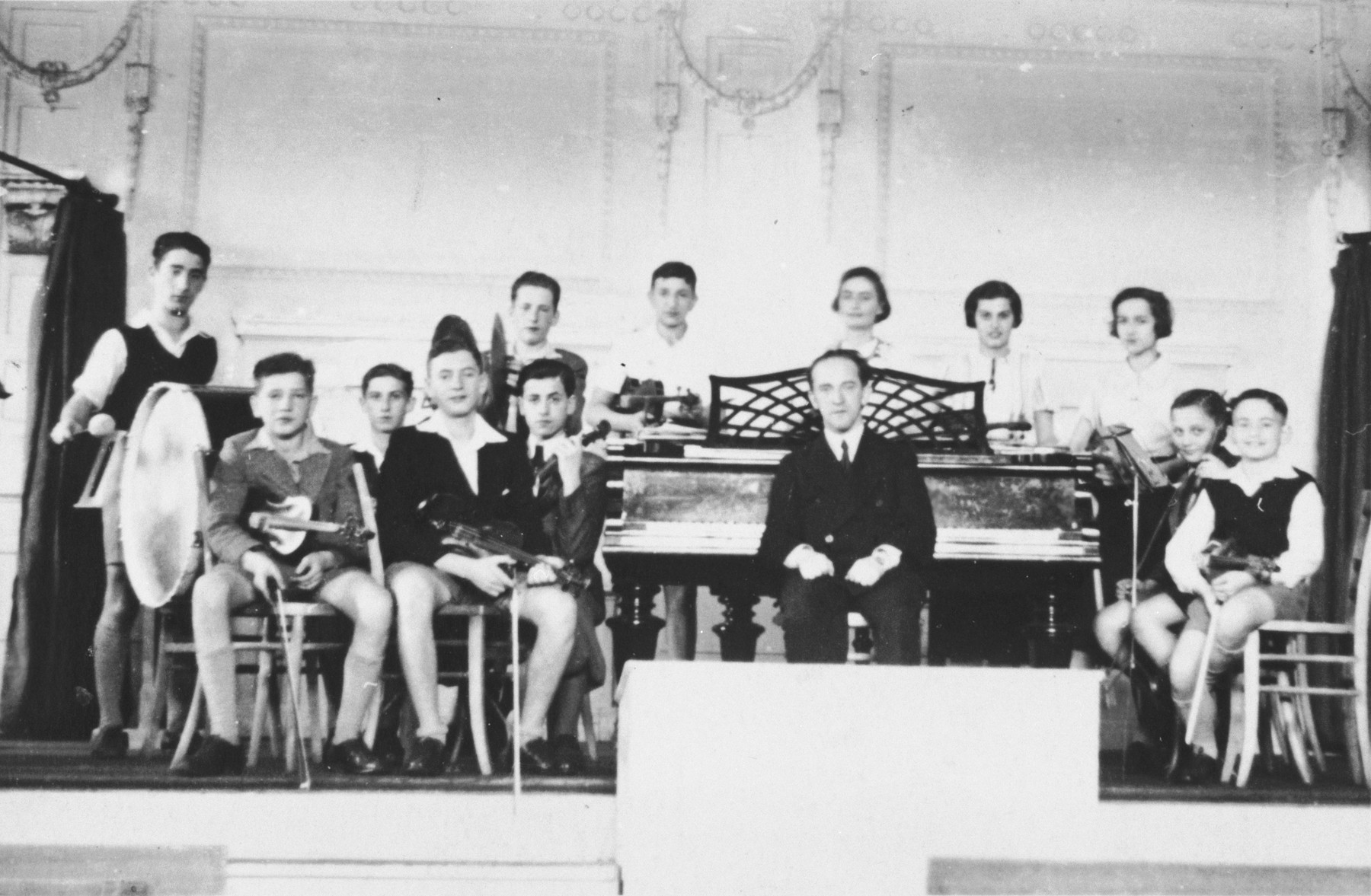 Group portrait of the members of the Jewish youth orchestra, sponsored by the Mittleschule der Judischen Gemeinde, with their musical instruments.  The conductor, Herr Loewy, is seated at the piano.  Ruth Cohn is pictured in the second row on the far right holding her violin.