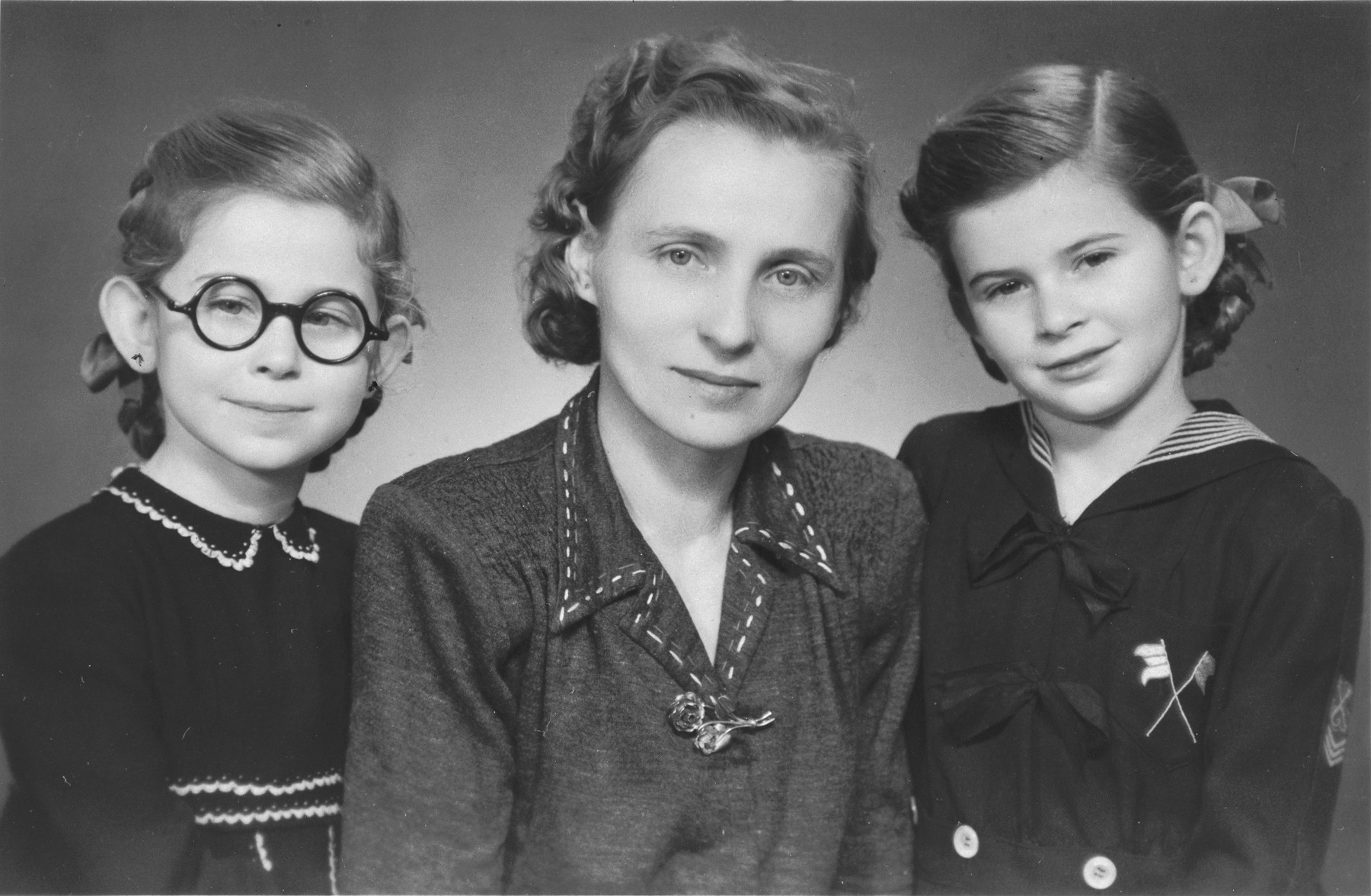 Studio portrait of two Jewish sisters with their rescuer after the war.  Pictured are Renate (right) and Sylvia Schonberg (left) with their nanny and rescuer, Frantiska Prva.