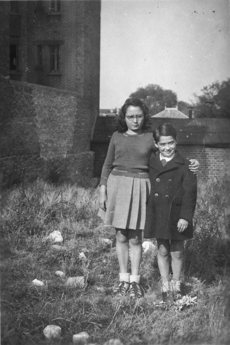 Denise and Jean-Claude Bystryn stand in a field next to their apartment house in Colombes after the war.