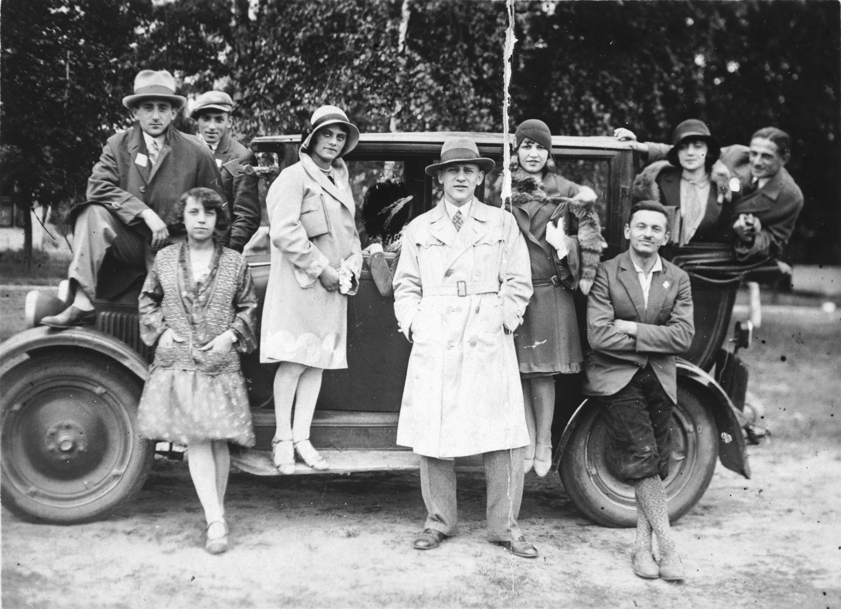 Frajda Fajerman (lower left) leans against an automobile surrounded by her factory coworkers.