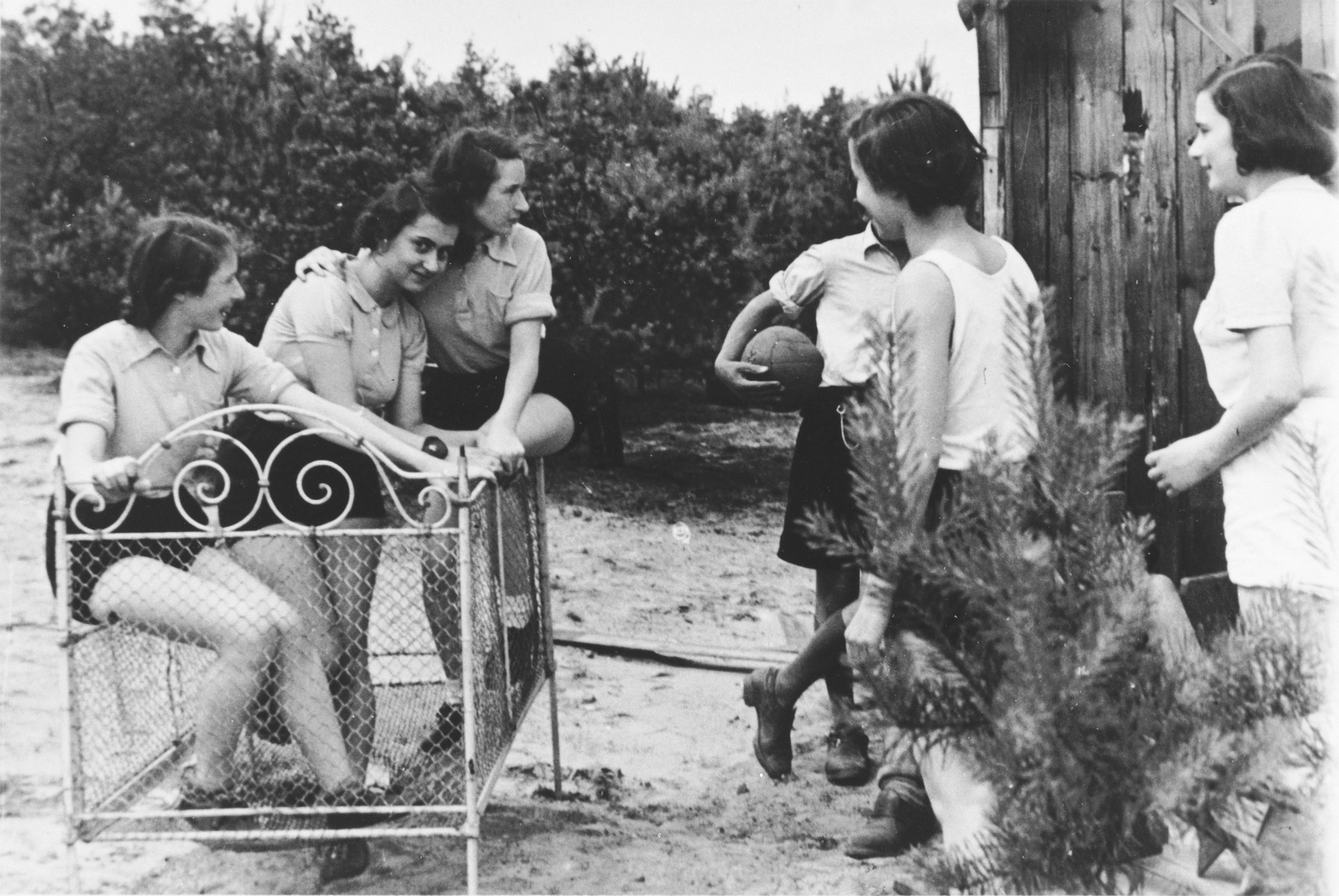 German-Jewish teenage girls gather with sports equipment in front of a rustic wooden building while on a Sunday outing to the country.  Among those pictured is Ruth Cohn.  She left on a Kindertransport to England two months later.