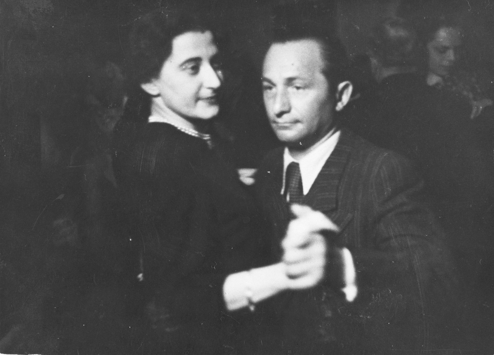 Close-up portrait of Lusia and Henryk Eichenholz dancing together.