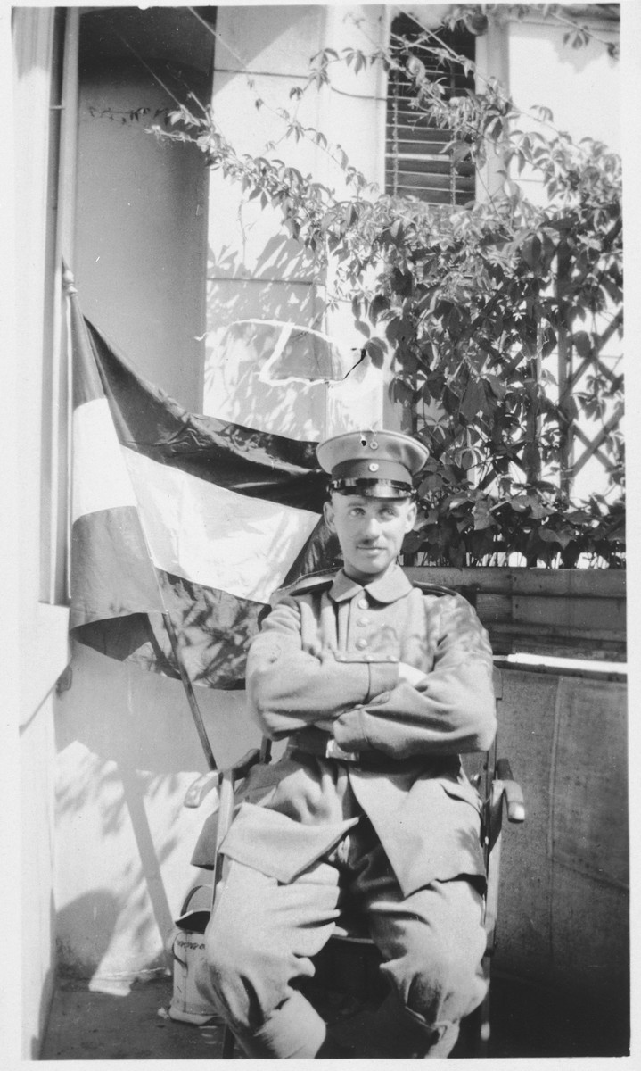 Werner Cohn, a German-Jewish soldier, sits outside his home in his army uniform next to a German flag.