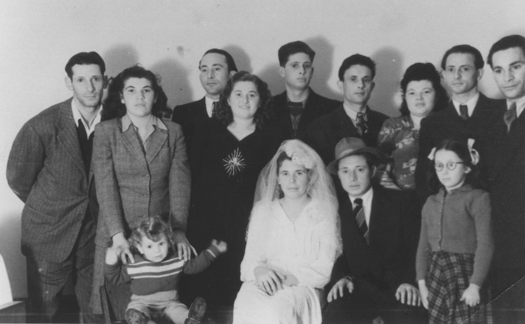 Wedding portrait of Pinkus Gipsman and Etta Falkovics in the Bari displaced persons camp.  At least five different brides wore this wedding dress in the Bari DP camp.  Etta's sister Tauba (Falakovics) Schechter, her husband Isidor and daughter Miriam are pictured on the left.