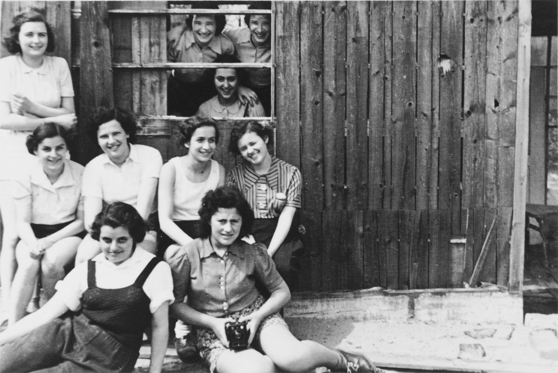 Group portrait of German-Jewish teenage girls in front of a rustic wooden building while on a Sunday outing to the country.  Among those pictured is Ruth Cohn.  She left on a Kindertransport to England two months later.