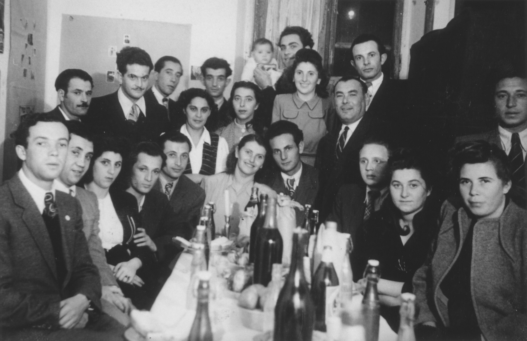 A group of friends celebrates the wedding of  Jacob and Miriam Schwimmer in the Bari dispaced persons camp.   Among those pictured is Jerome (Jacob) Hollander, seated second from the left.