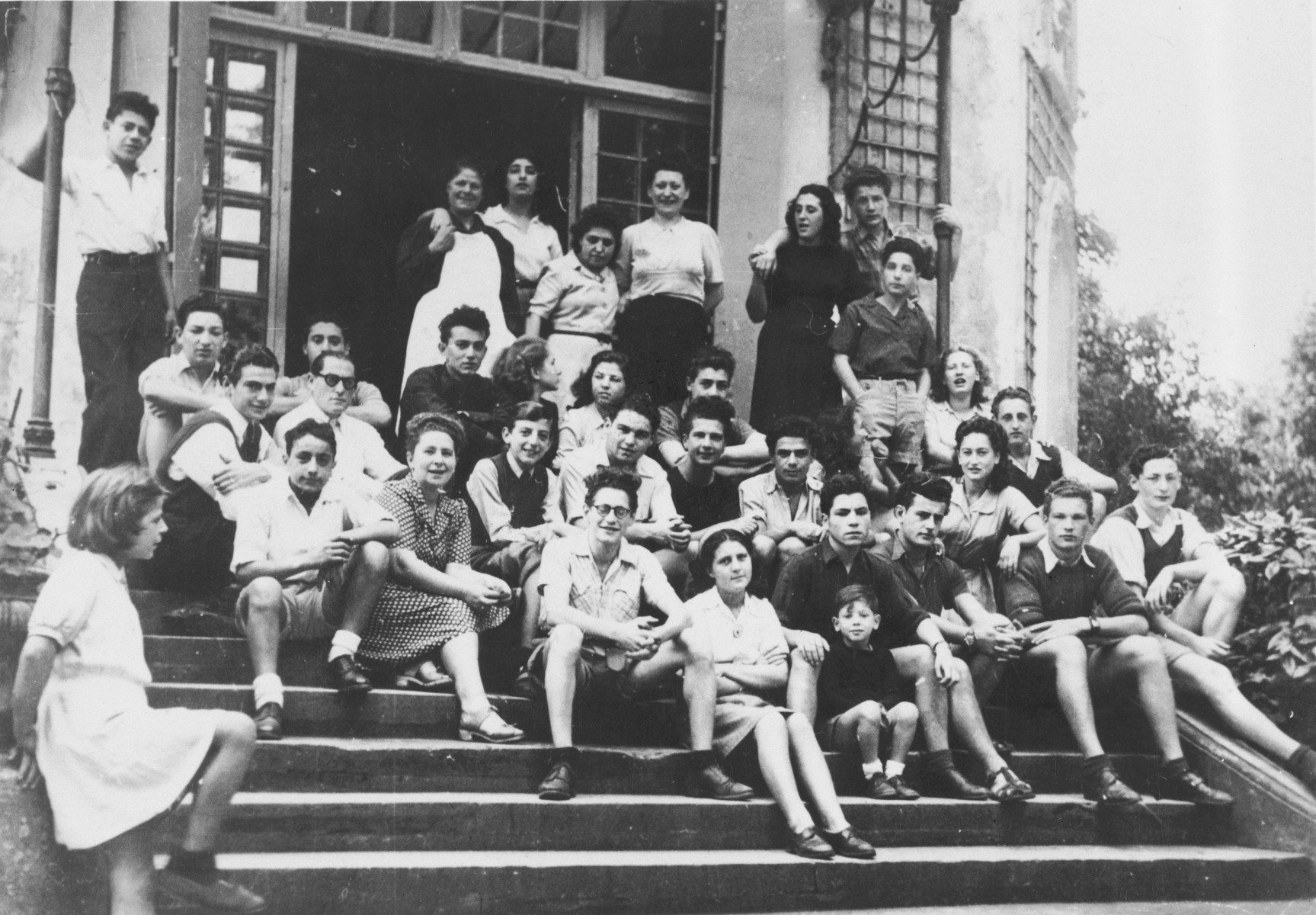 Group portrait of the students and staff of the Malmaison children's home.  Among those pictured are the director, Dr. Cecile Wexler, Jean Maurice Bito, Toto, Anna, Jacques Korman and Simon Noz (seated on fifth step, far right, with light colored dress).