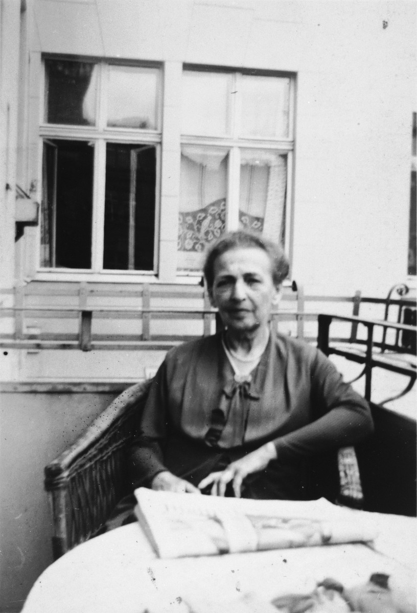 A German-Jewish woman sits on a porch on a wicker chair with her newspaper.  Pictured is Olga Cohn, grandmother of the donor.