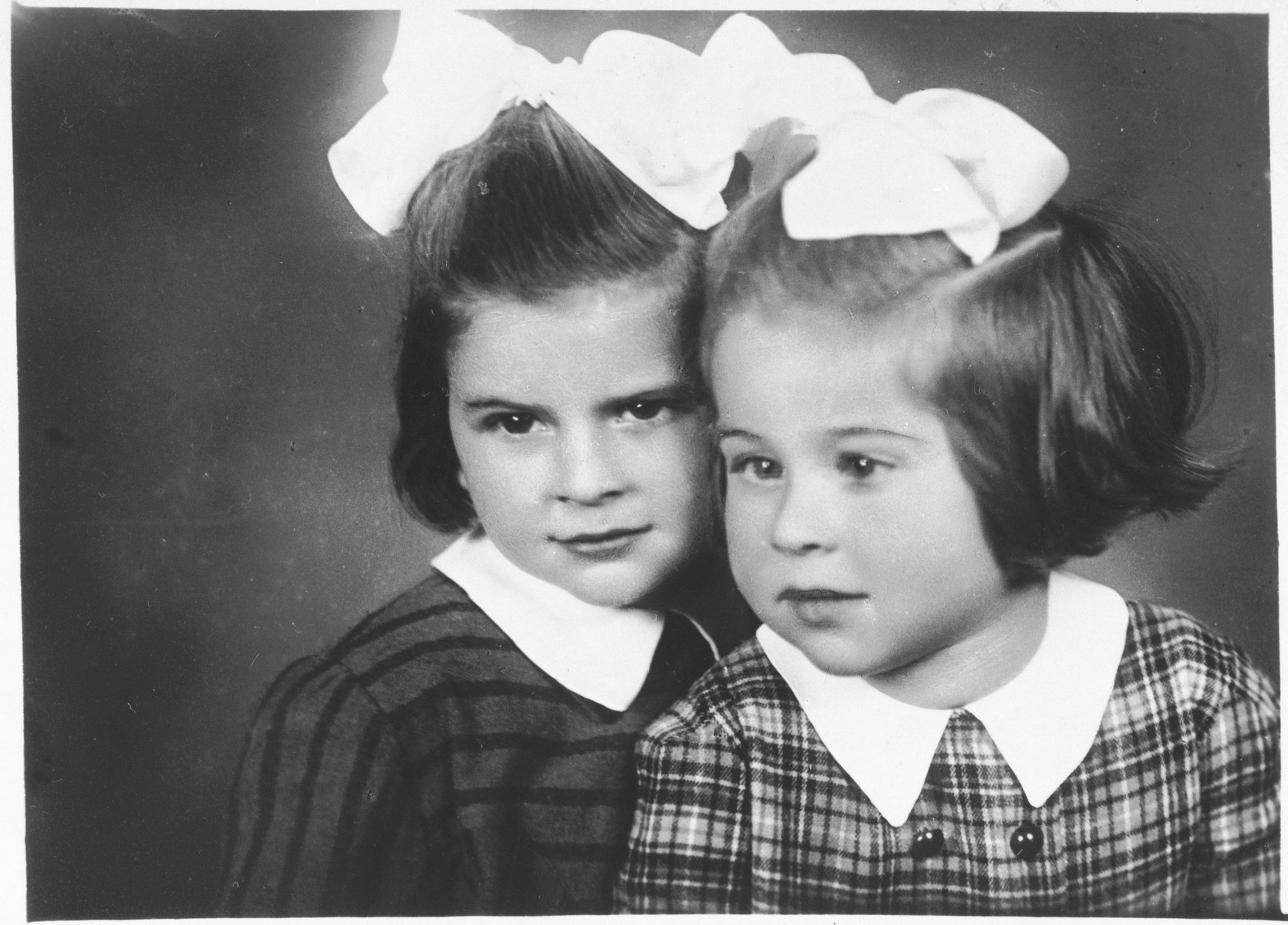 Studio portrait of two young Jewish sisters in Cop.  Pictured are Renate (left) and Sylvia Schonberg.
