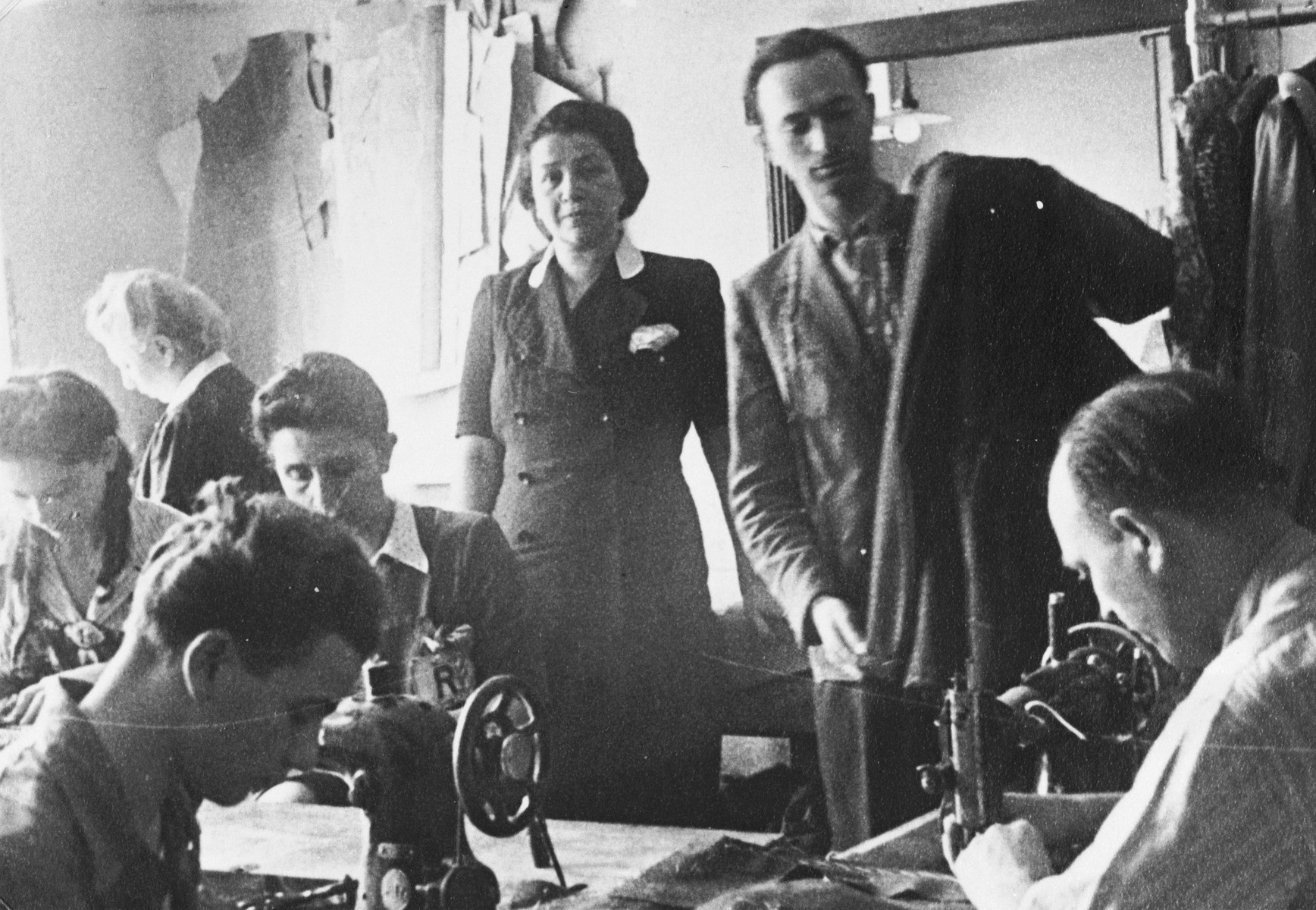 Employees work at sewing machines in the Julius Madritsch clothing workshop.  Bronislaw Eichenholz is seated in the front left.  Behind him are Dziunia and Lusia Eichenholz.  Standing include Paula (middle) and Mrs. Minder.