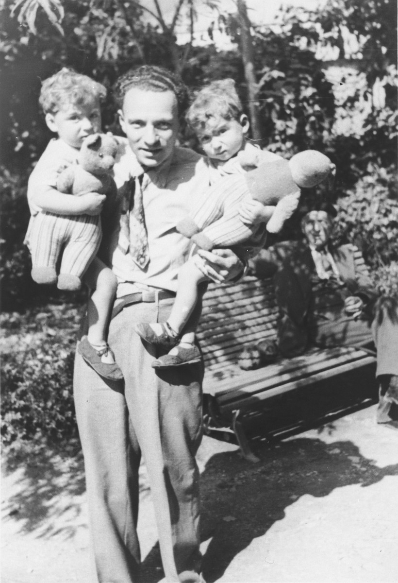 Raoul Haas holds his two-year old twins, Jean and Pierre.