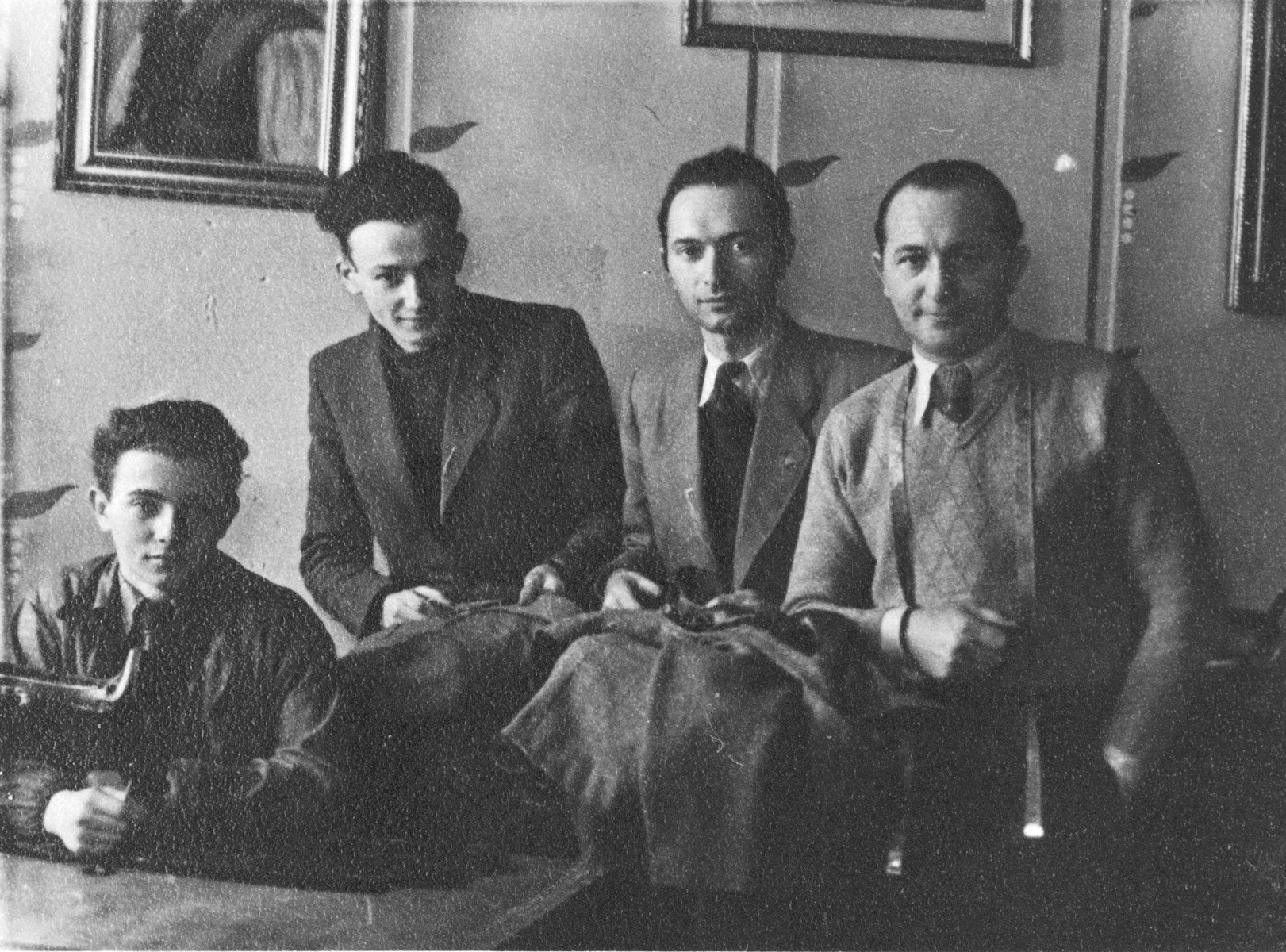 Employees work in the Julius Madritsch clothing workshop in the Krakow ghetto.  Henryk Eichenholz is on the far right and his son Bronek is on the left.