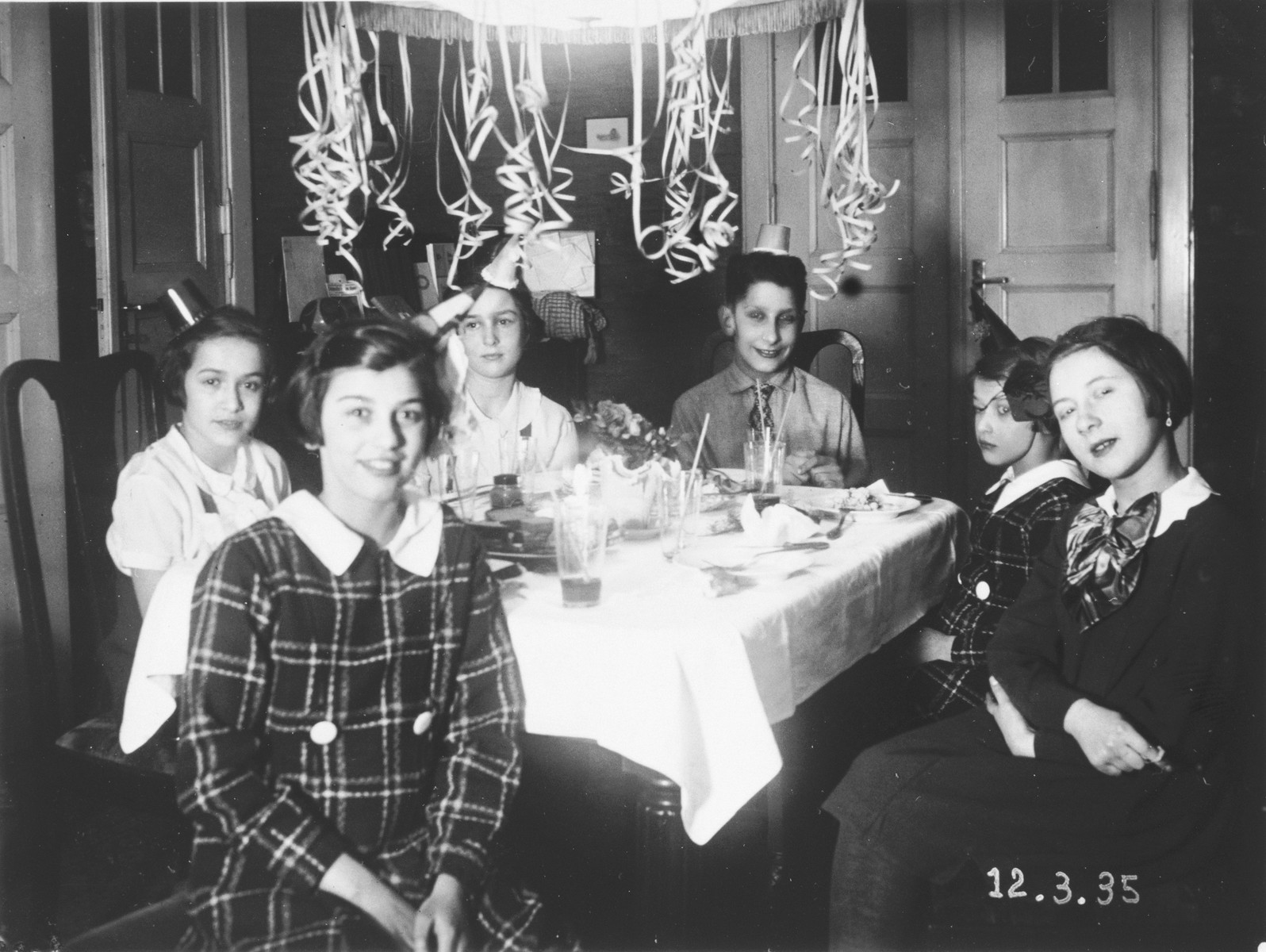 Young German-Jewish teenagers wearing party hats gather for a birthday party in a room decorated with paper streamers.  Those pictured include the birthday girl, Hannelore Kittle and Ruth Cohn (seated on left).