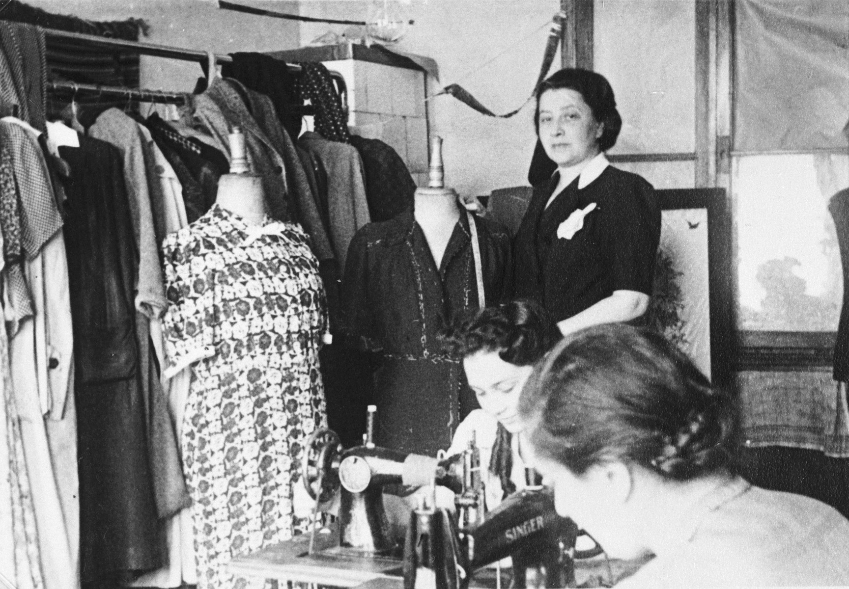 Female employees work in the Julius Madritsch Ladies' Custom Shop.  Standing is the manager Mrs. Minder and seated at the machine is Dziunia Eichenholz.