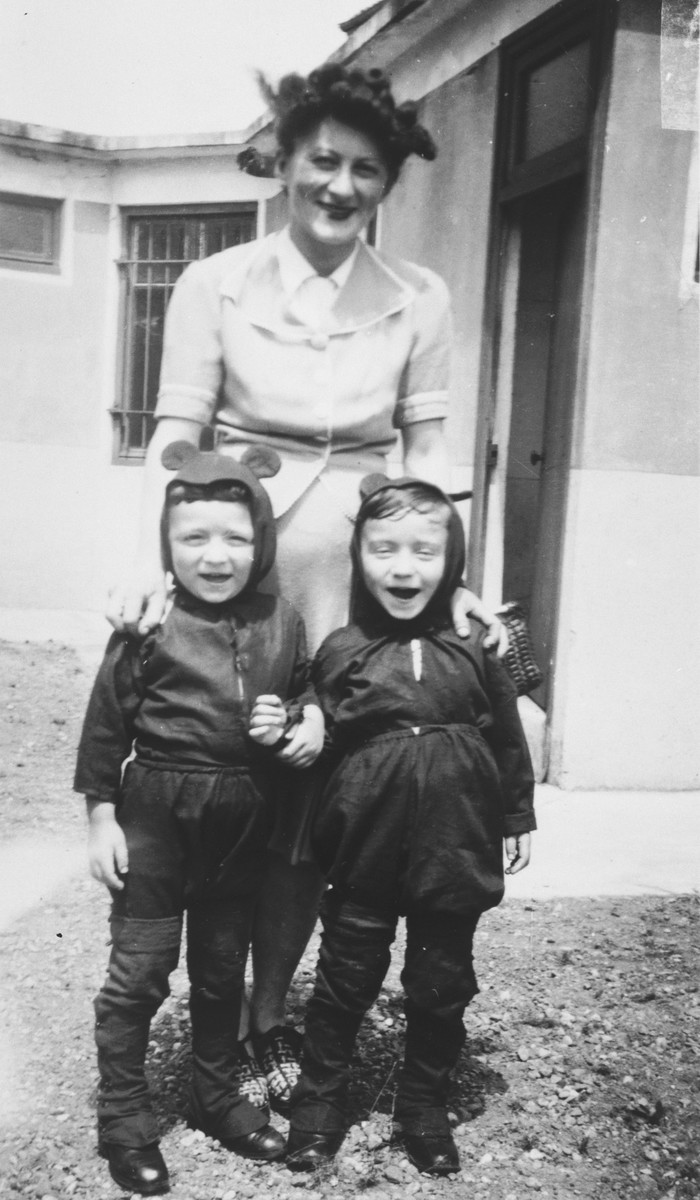 Portrait of Helene Haas stands with her four-year old twins, Jean and Pierre who are wearing costumes, while living as a family under false papers in Couzon.
