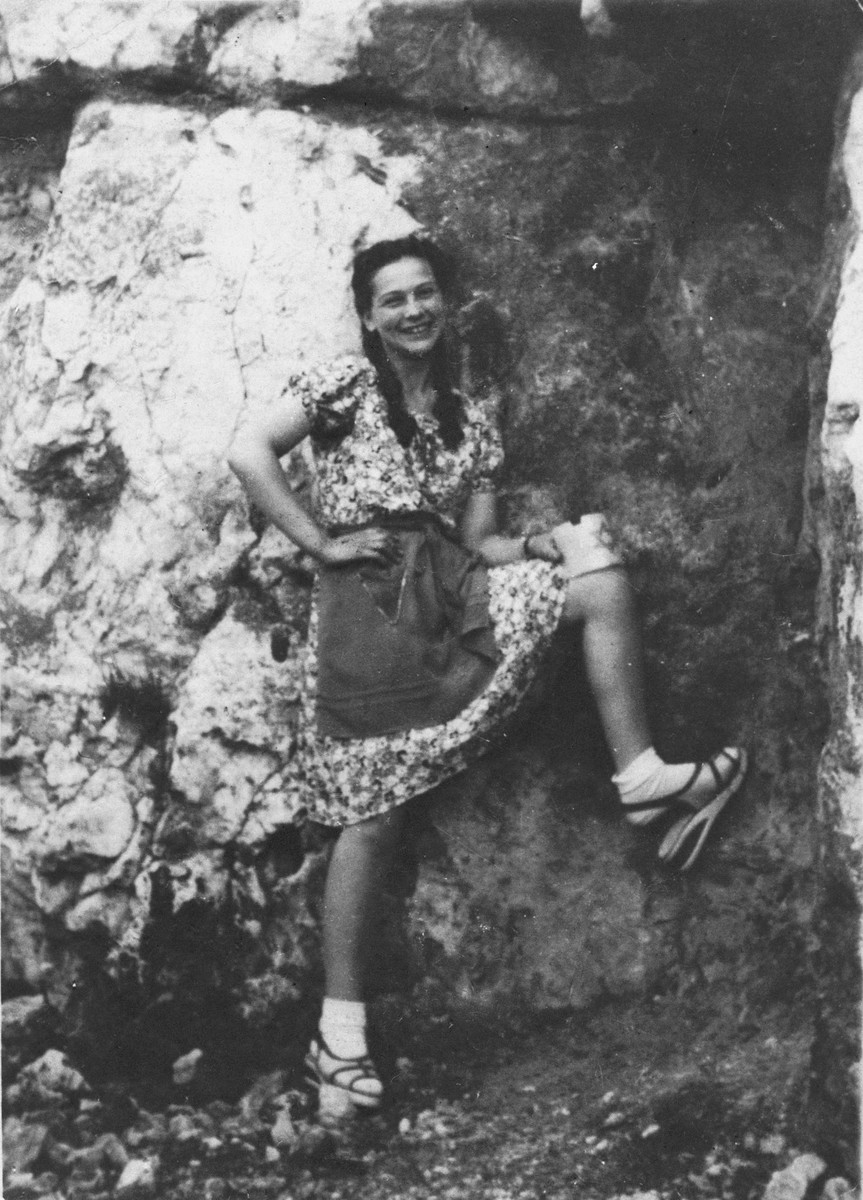 Dziunia Eichenholz playfully poses in the Krakow ghetto while balancing her armband on her knee.