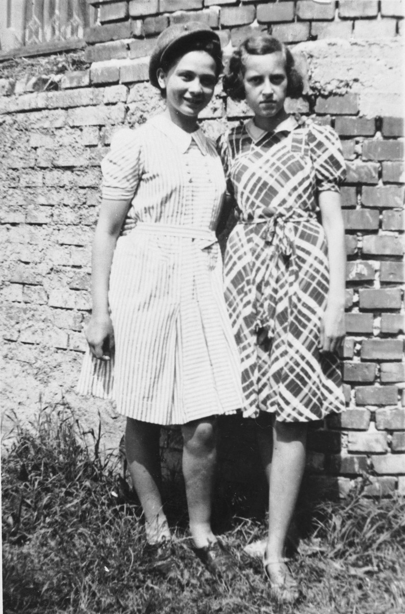 Close-up portrait of Dziunia Eichenholz and a school friend standing in front of a brick wall.