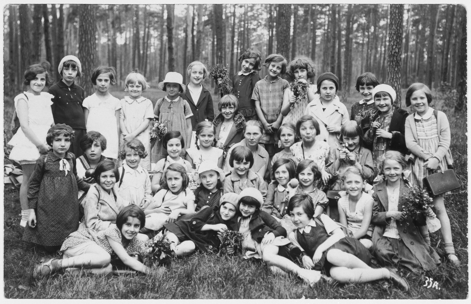 Group portrait of girls, about half of whom are Jewish, from the Hoenstaofen Strasse school, taken during a class outing in a wooded park.  Among those pictured is Ruth Cohn.
