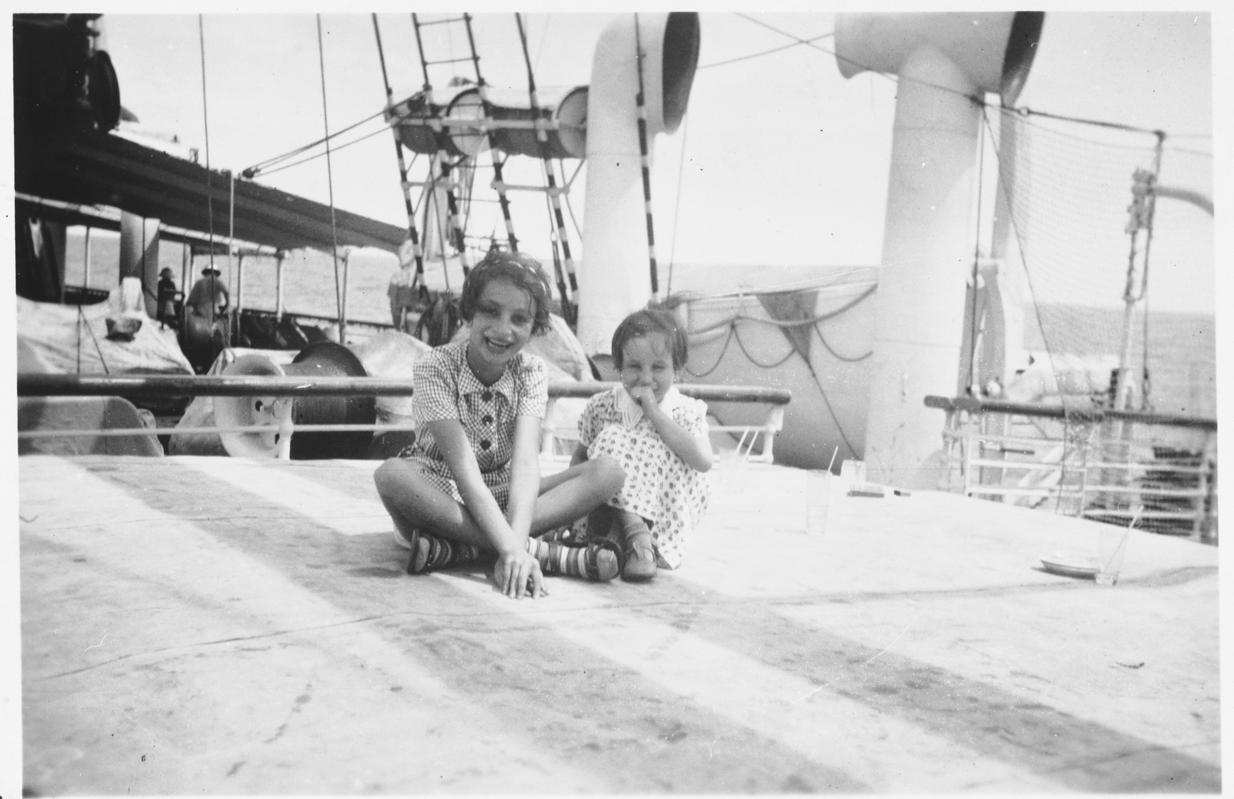 Two Jewish refugee children sit on the deck of the Usambara while en route to Africa.   Pictured are Gisela (right) and Inge Berg (left).