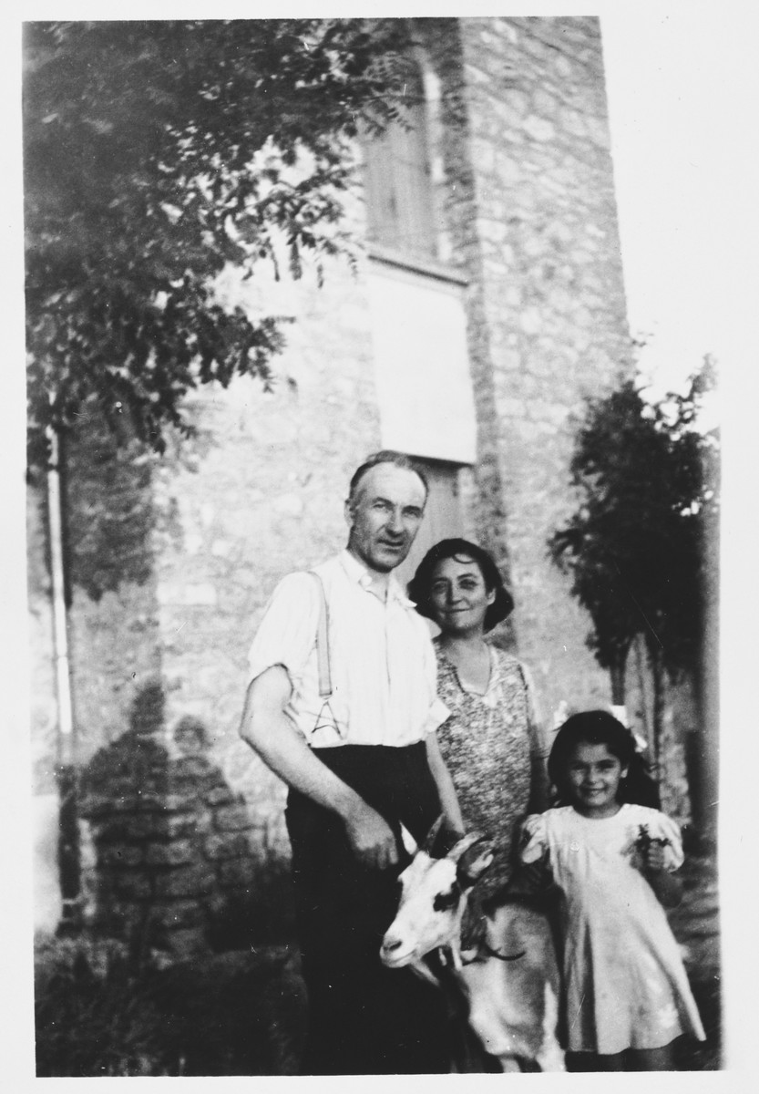 A Jewish child, Diane Popowski, poses with an adult couple and a goat in Montpellier, France.