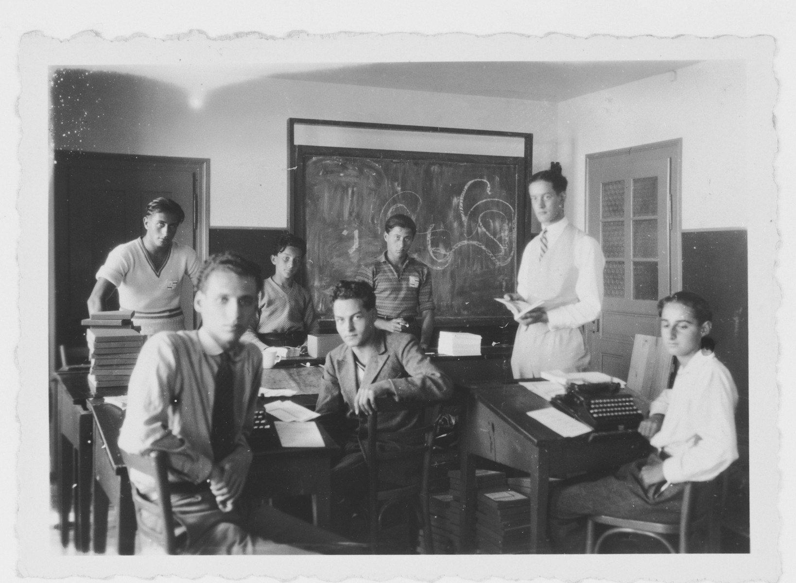 Italian teenagers sit by their desks in their high school classroom.  Mario Fabini is in the center in a suit.