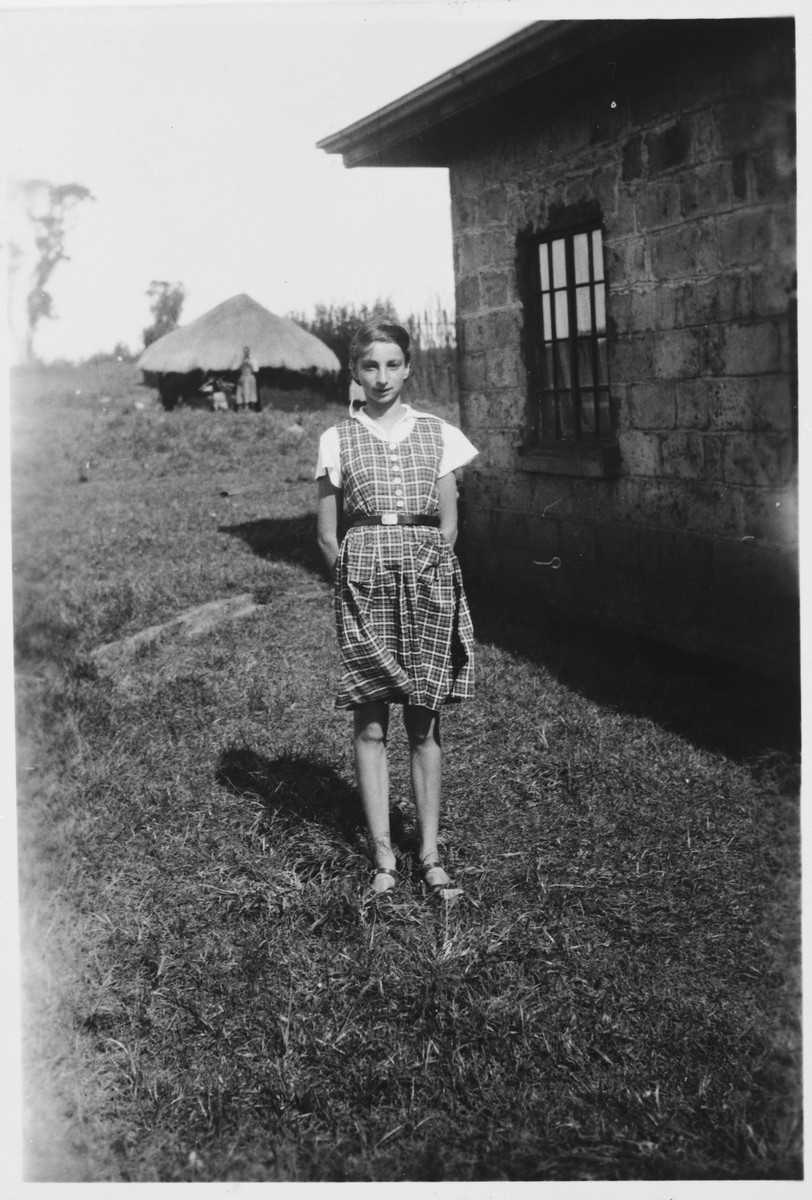 A Jewish refugee child poses outside her family's farmhouse near Limuru, Kenya (Kiambu district), where they found refuge during World War II.  Pictured is Inge Berg.  A thatched roof shelter can be seen in the distance.