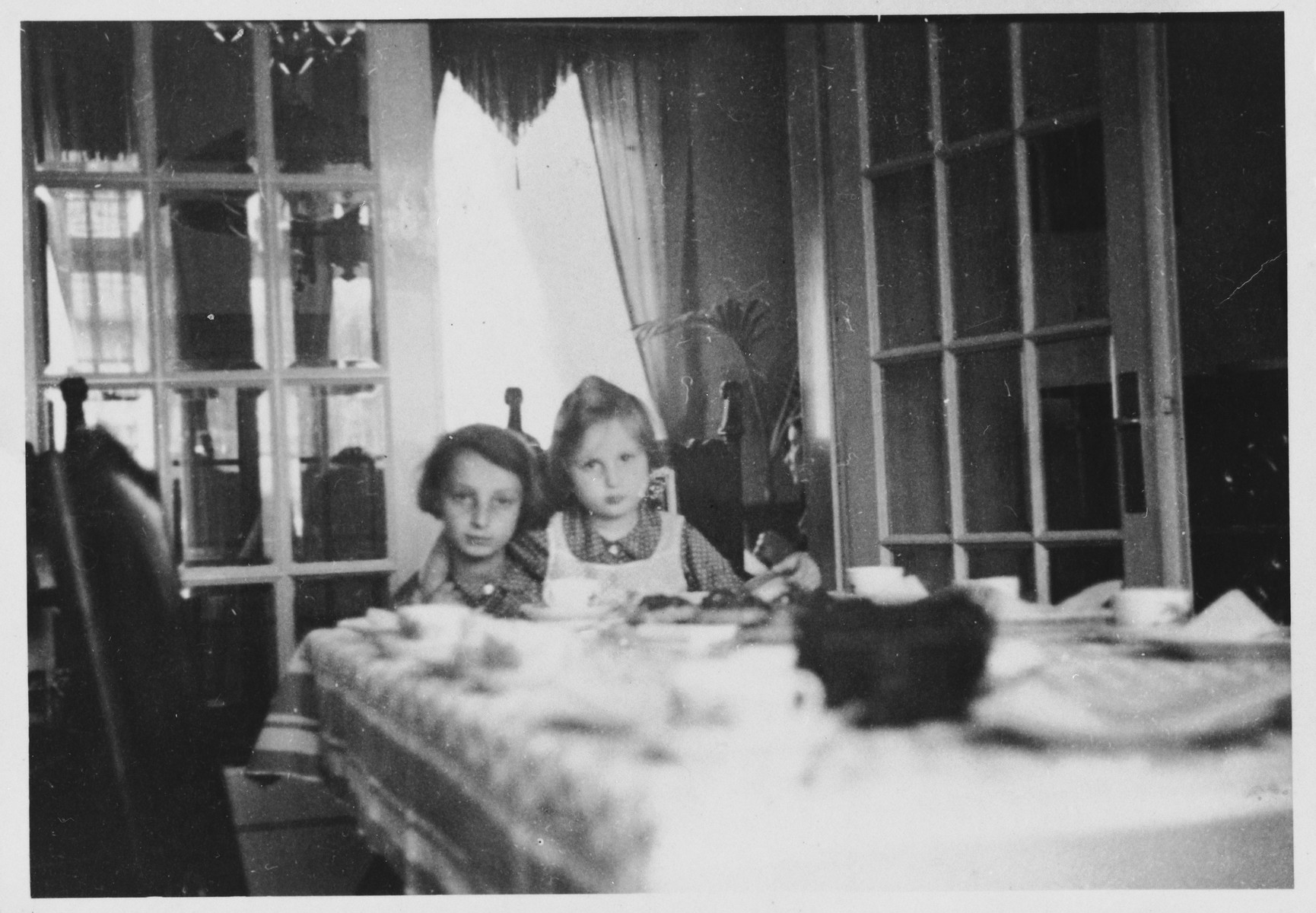 Two Jewish sisters sit together at the dining room table in their parent's farmhouse after hearing about the family's plans to emigrate from Germany.  Pictured are Gisela and Inge Berg.