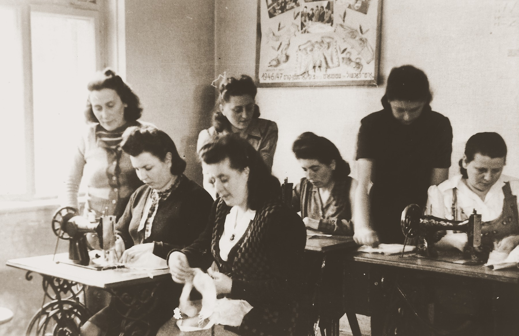 """F. Mandel teaches a class in corset making at the ORT vocational training school in the Stuttgart DP camp.  One image from the Stuttgart Jewish DP camp album entitled, """"Jidiszer D.P. Center UNRRA--P.C.IRO in Stuttgart,"""" compiled and photographed by Alexander Fiedel and dedicated to Moses Kornberg, head of the commissary."""