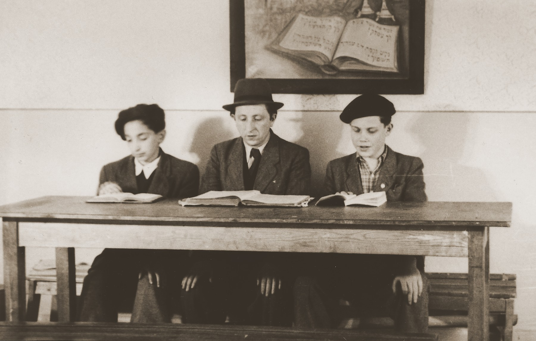 "An instructor teaches two boys religious texts in a cheder [religious elementary school] at the Stuttgart DP camp.  One image from the Stuttgart Jewish DP camp album entitled, ""Jidiszer D.P. Center UNRRA--P.C.IRO in Stuttgart,"" compiled and photographed by Alexander Fiedel and dedicated to Moses Kornberg, head of the commissary."