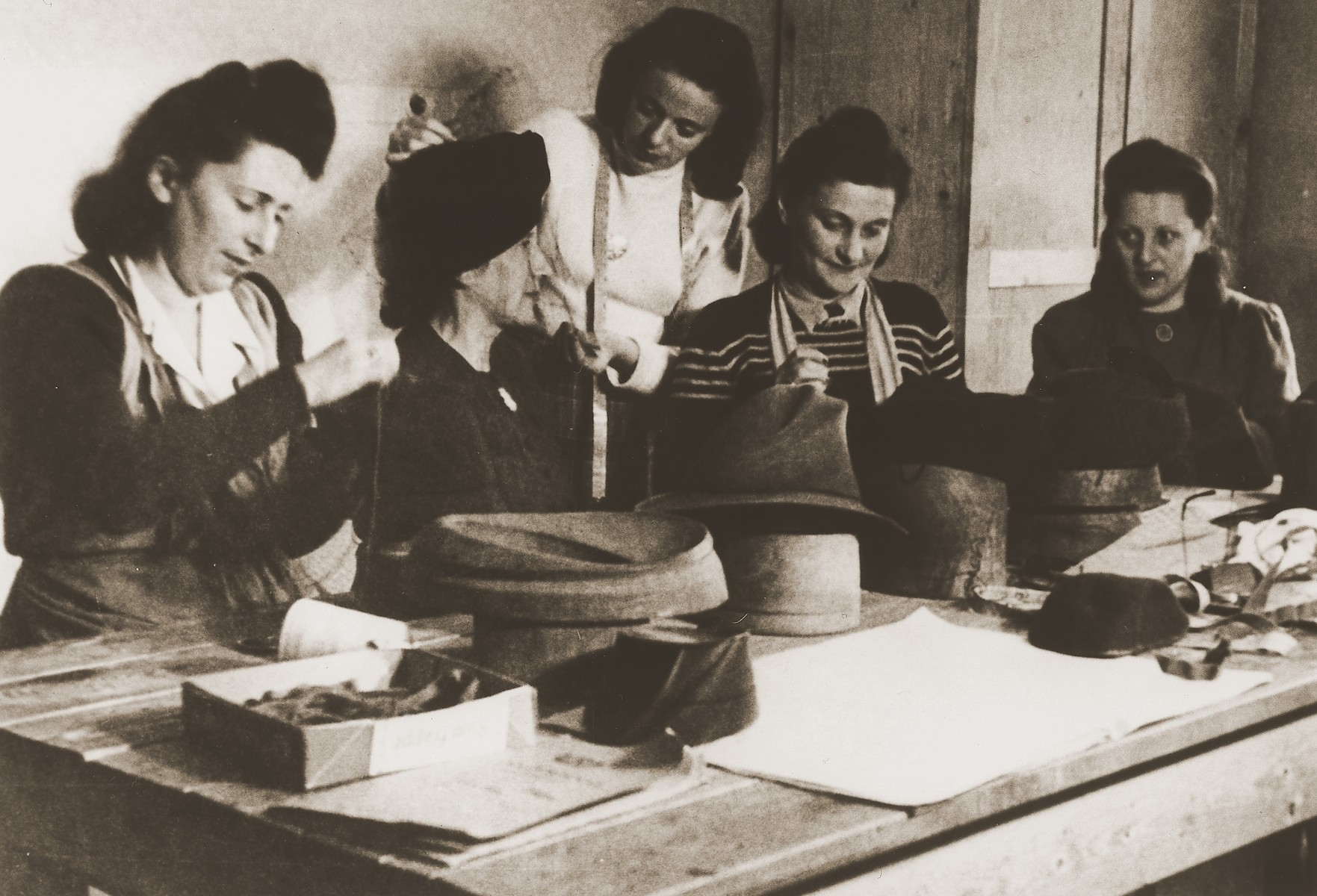 "M. Kempner instructs four women in the trade of hat making at the ORT vocational training school in the Stuttgart DP camp.  One image from the Stuttgart Jewish DP camp album entitled, ""Jidiszer D.P. Center UNRRA--P.C.IRO in Stuttgart,"" compiled and photographed by Alexander Fiedel and dedicated to Moses Kornberg, head of the commissary."