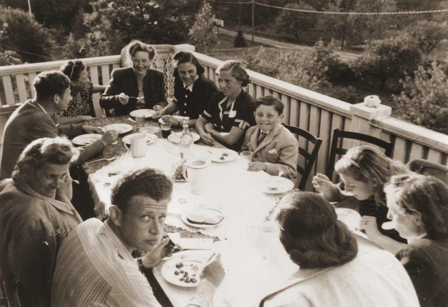 A group of Jewish DPs living in Sweden have dinner on a balcony.