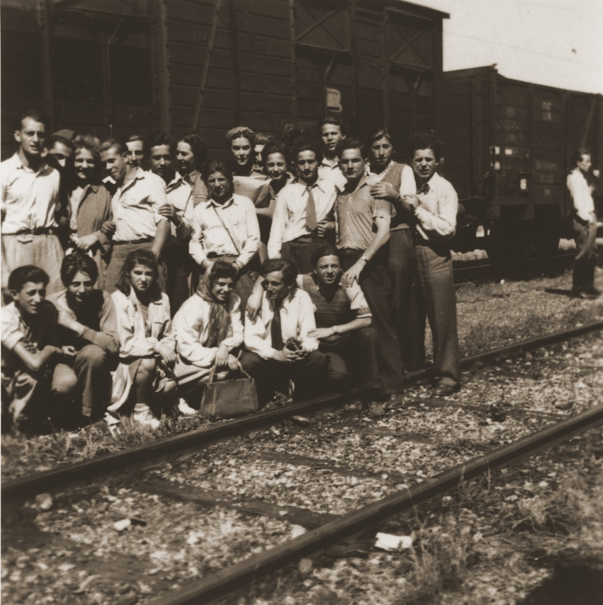 A group of young men and women from the Kloster Indersdorf DP children's center pose in front of a train before their departure.  Among those pictured is Genia Edlerman, bottom row, third from the left.