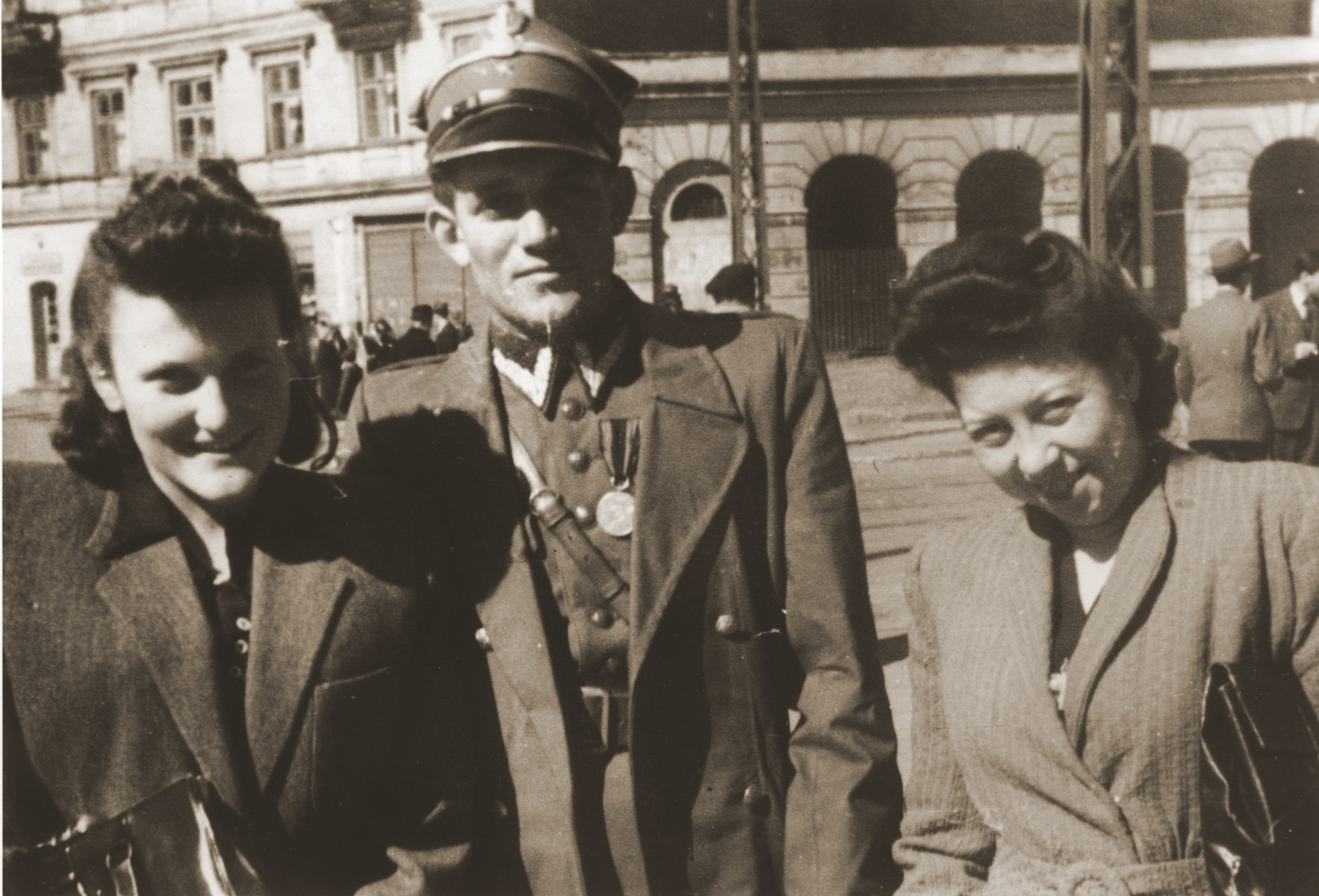 Felicja Berland and a friend pose with a Jewish soldier in the Polish Army on a street in Lodz.