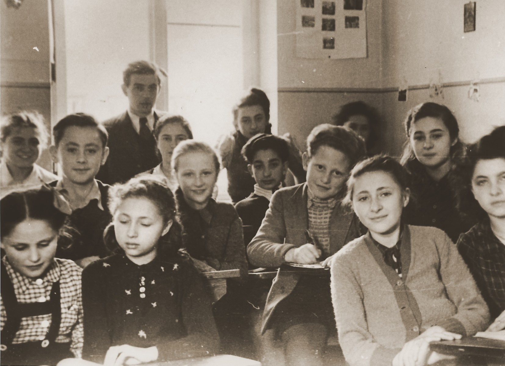 "A classroom of students listens to a lecture in Yiddish by their teacher Chaim Szmerick in the Stuttgart DP camp.  Among those pictured are: Lova Warszawczyk (left, second row, now Larry Warick), David Hoffman (second row, second from right),  ? Hoberman (first row, second from right), Hadasa Gassenbauer (first row on left), and Bronia Graudens (back, left corner).  One image from the Stuttgart Jewish DP camp album entitled, ""Jidiszer D.P. Center UNRRA--P.C.IRO in Stuttgart,"" compiled and photographed by Alexander Fiedel and dedicated to Moses Kornberg, head of the commissary."