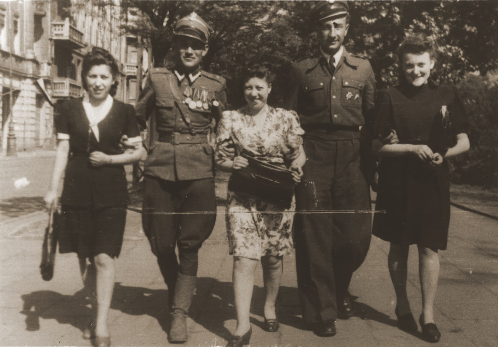 Felicja Berland (center) and two girlfriends walk along a street in Lodz with two Jewish lieutenants in the Polish Army.