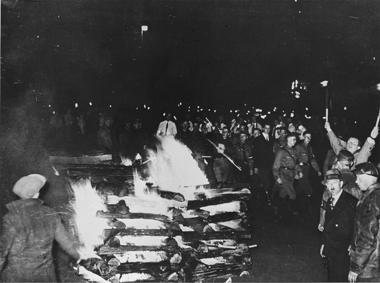 """SA members and university students march in a torchlight  procession around the bonfire of """"un-German"""" books on the Opernplatz."""
