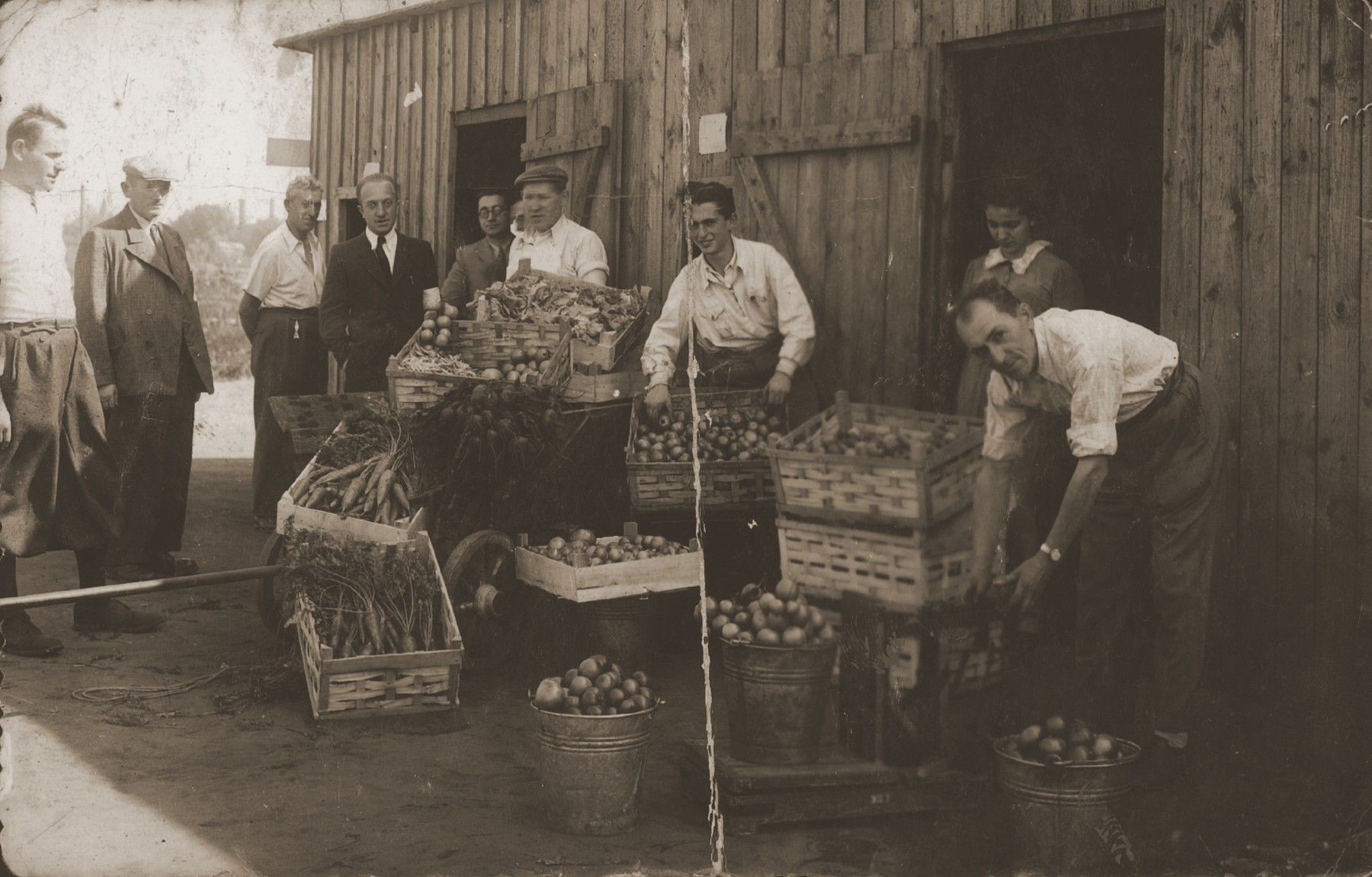 Jewish workers put out their produce in boxes and pails in front of a wooden shed.