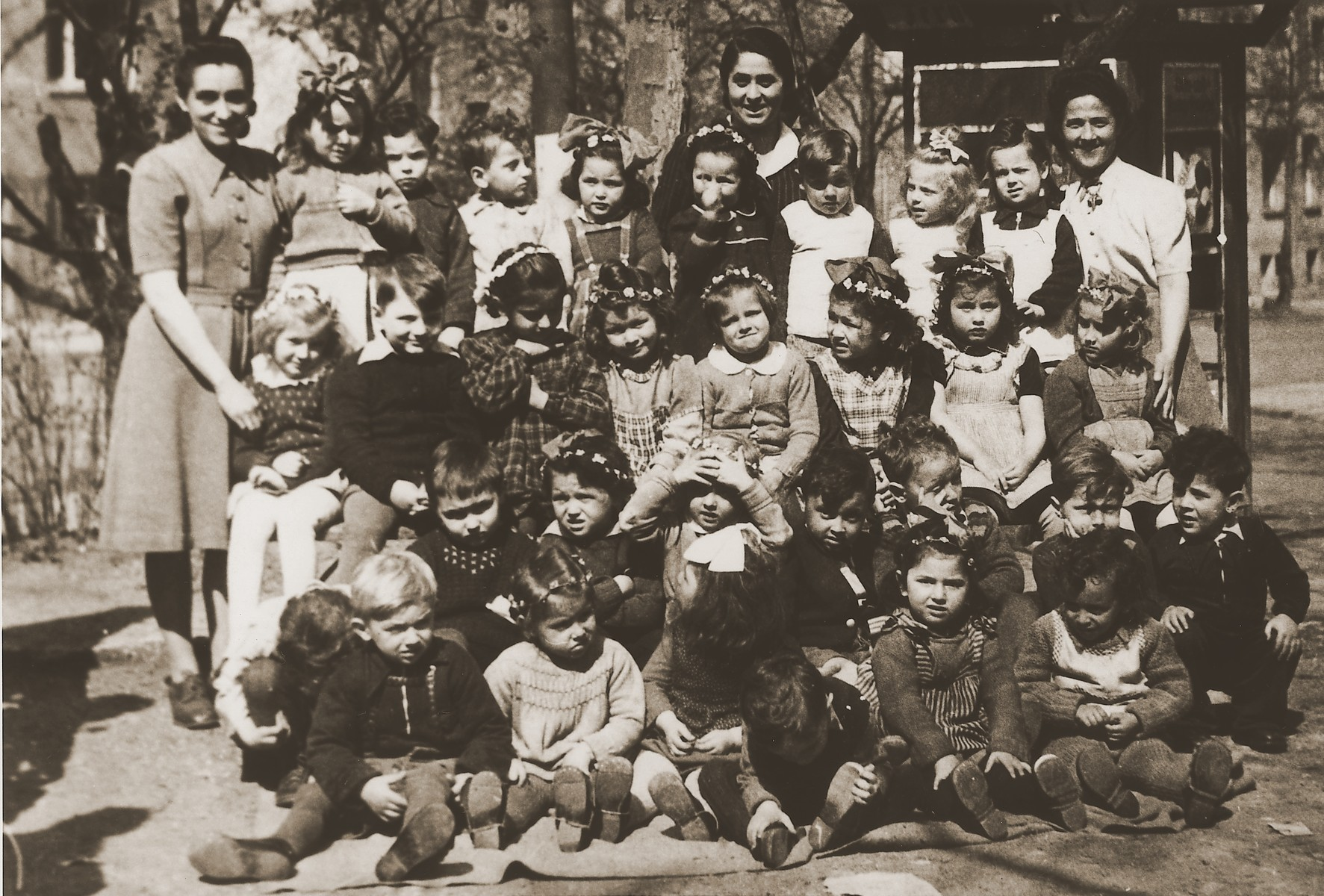 """Group portrait of a Kindergarten class at the Stuttgart DP camp.  One image from the Stuttgart Jewish DP camp album entitled, """"Jidiszer D.P. Center UNRRA--P.C.IRO in Stuttgart,"""" compiled and photographed by Alexander Fiedel and dedicated to Moses Kornberg, head of the commissary.  Pictured in the middle row far right is Golda Solcer."""