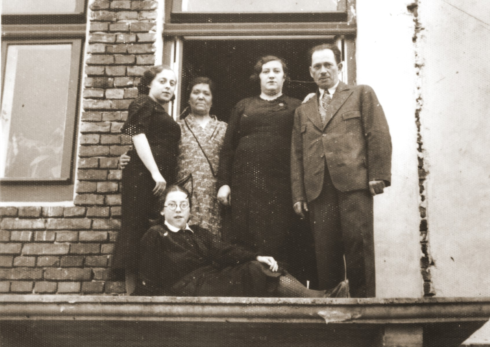 Members of the Berland family on the unfinished balcony of their home in Chelm.  Pictured standing from left to right are: Hela Zonenszein; Chaya Rachel Hilf; Sara Berland and Abraham Berland.  Felicja Berland lies in front of them.