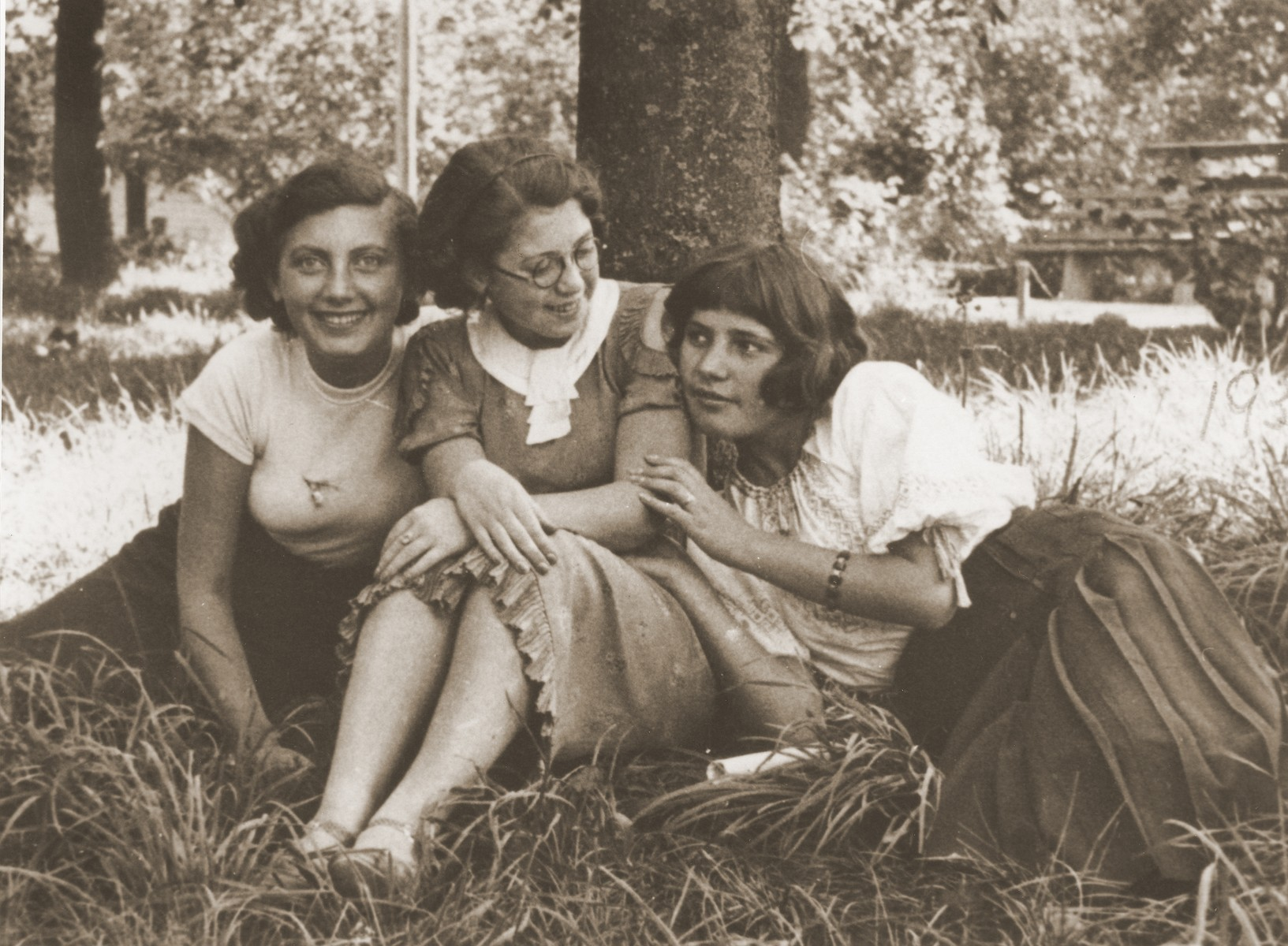 Three Jewish girlfriends in a park in Chelm.    Pictured from left to right are: Genia Karpenkopf, Felicja Berland, and Hanka Aljos.