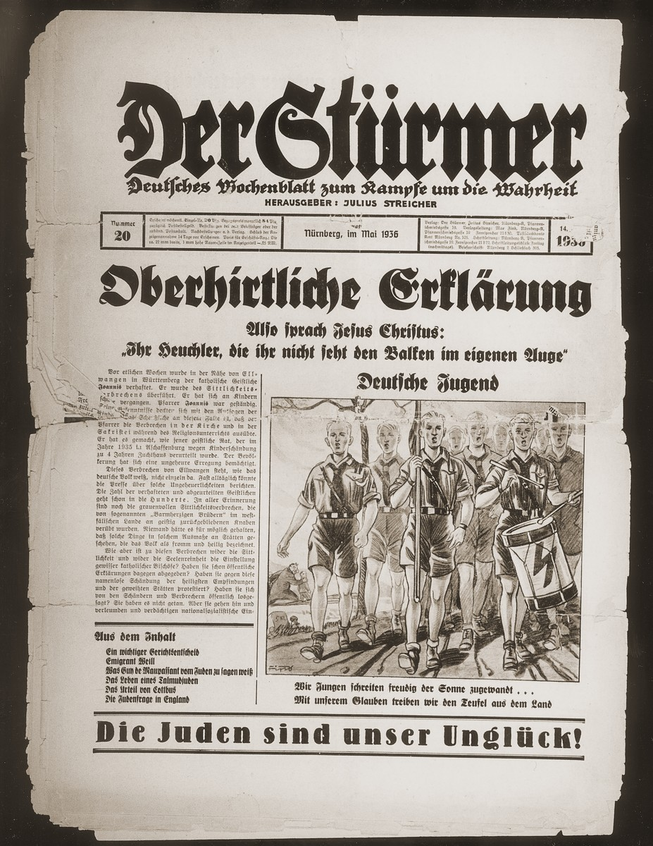 "Front page of the Nazi publication, Der Stuermer, with a cartoon depicting a group of Hitler Youth marching forth to drive the forces of evil from the land.  The caption under the cartoon reads, ""We youth step happily forward facing the sun... With our faith we drive the devil from the land.""  The headline reads, ""Declaration of the Higher Clergy/So spoke Jesus Christ: You hippocrites who do not see the beam in your own eyes."