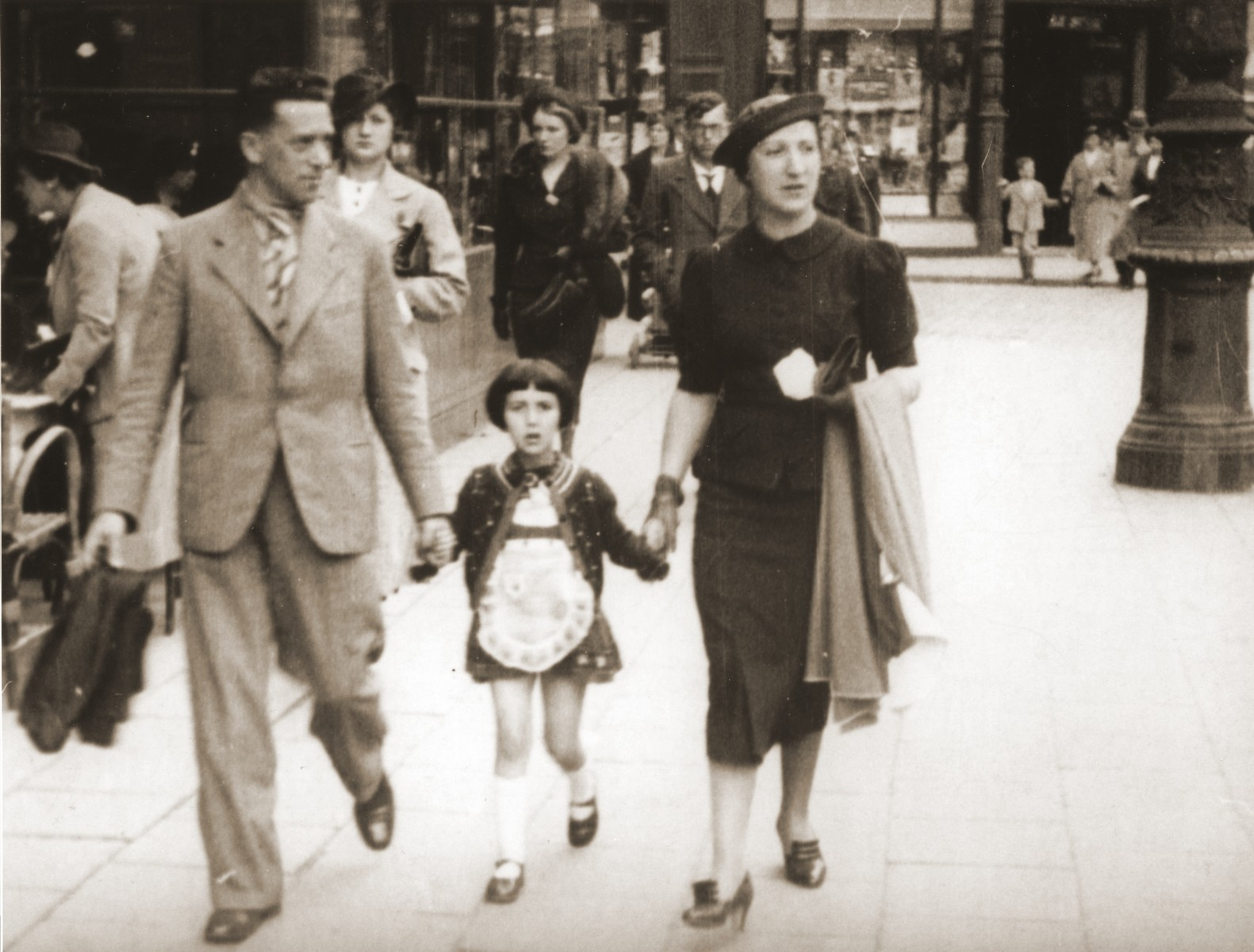 Michael and Manja Schadur stroll along a commercial street in Antwerp with their daughter. Benita.