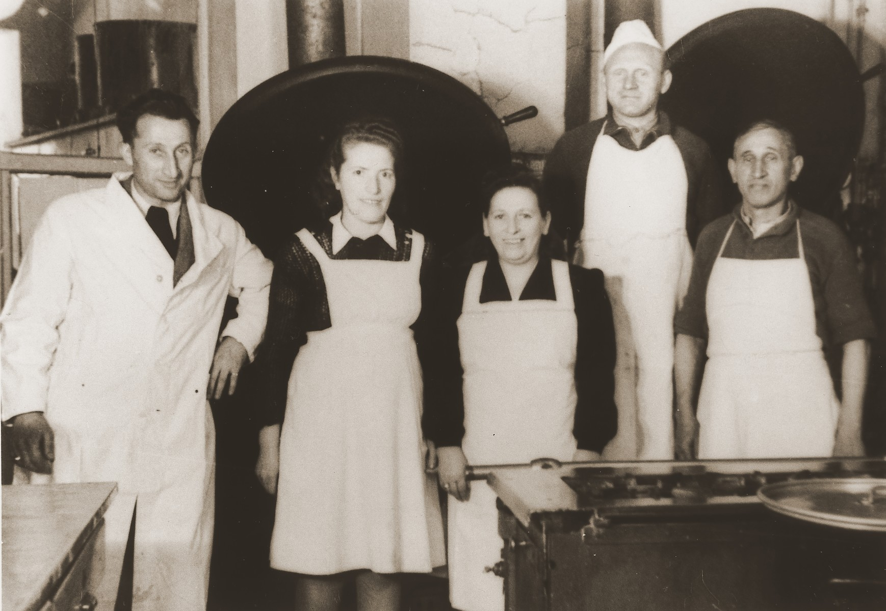 "Chef J. Klepfisz (left) poses with four members of the kitchen staff at the Stuttgart DP camp.  One image from the Stuttgart Jewish DP camp album entitled, ""Jidiszer D.P. Center UNRRA--P.C.IRO in Stuttgart,"" compiled and photographed by Alexander Fiedel and dedicated to Moses Kornberg, head of the commissary."