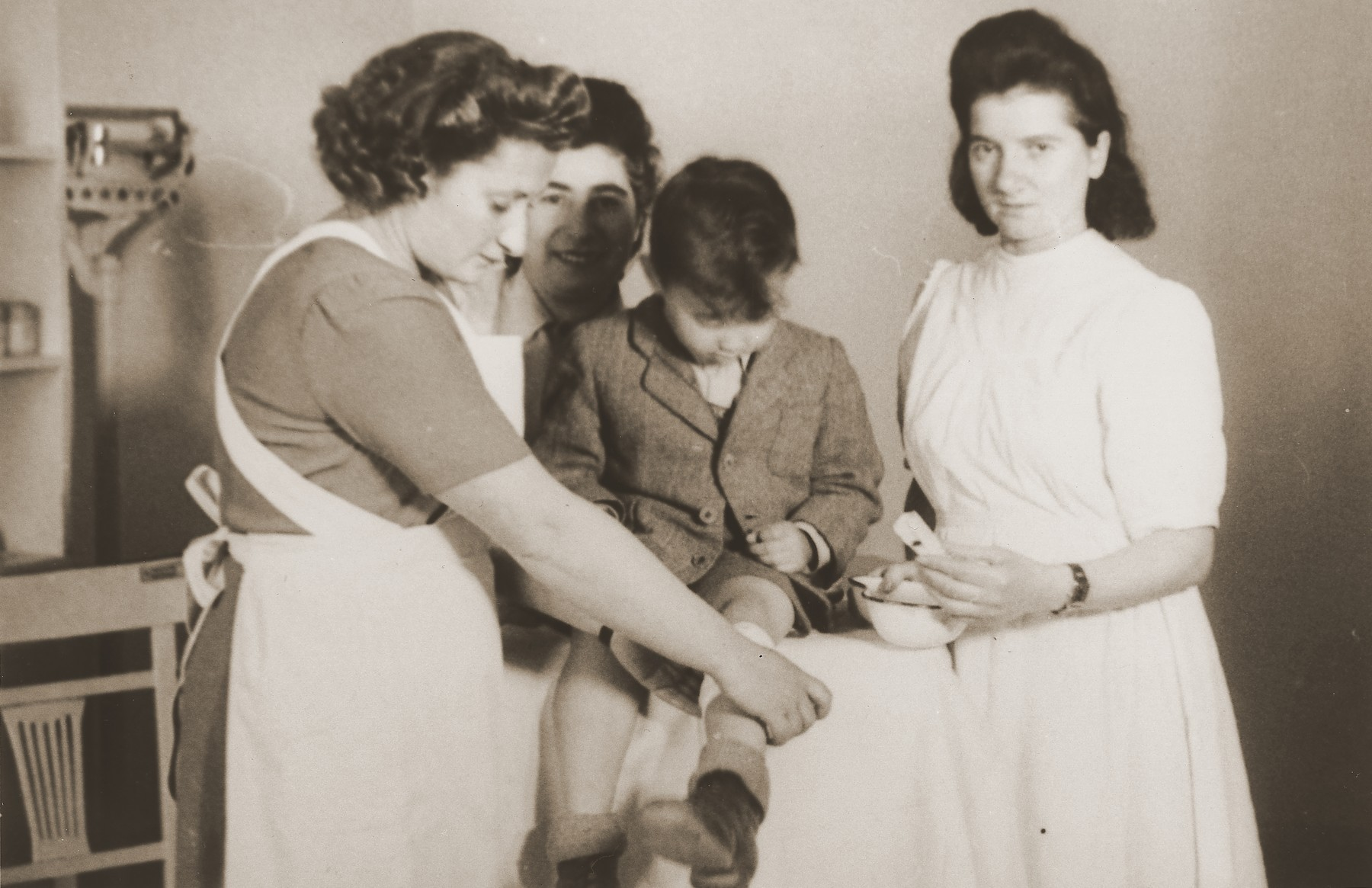 """Nurses bandage the leg of a young boy at the clinic in the Stuttgart DP camp.  One image from the Stuttgart Jewish DP camp album entitled, """"Jidiszer D.P. Center UNRRA--P.C.IRO in Stuttgart,"""" compiled and photographed by Alexander Fiedel and dedicated to Moses Kornberg, head of the commissary."""