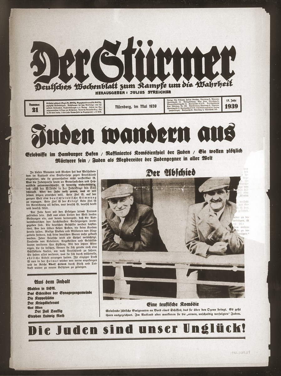 """Front page of the Nazi publication, Der Stuermer, with a photograph of Jewish emigrants on the deck of a ship.  The caption reads, """"The Departure/A devilish comedy/Grinning Jewish emigrants on board a ship that will take them across the ocean.  They are doing very well.  In foreign lands, however, they make themselves out to be 'poor, innocent, persecuted' Jews.""""  The headline reads, """"Jews Emigrate/Experiences in the port of Hamburg/The clever comedy of the Jews/All of a sudden they claim to be martyrs/Jews as the makers of anti-Semites [Judengegner] all over the world."""""""