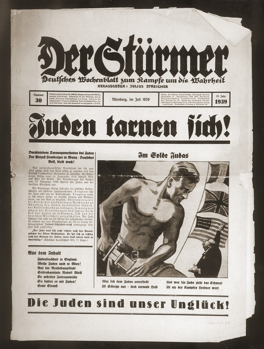 "Front page of the Nazi publication, Der Stuermer, with an anti-Semitic caricature depicting the Jew as one who tries to subvert others.  The caption reads, ""In the pay of Judas/He who subordinates himself to the Jews is only a dwarf never a hero/And he who draws his sword for Judah is never worth the laurels.""  The headline reads, ""Jews disguise themselves/The methods of Jewish disguise/The Hamburger trial in Mainz/German people stay awake!"""